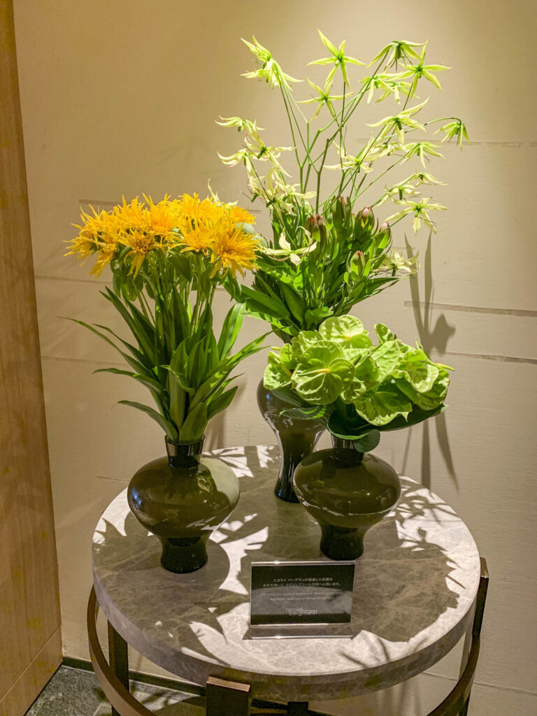 Three vases (two with green flowers and one with yellow flowers) sitting on a table near the spa.