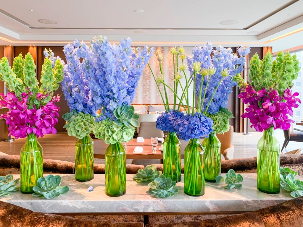 Colorful flowers and succulents in green vases at Motif restaurant inside Four Seasons Tokyo