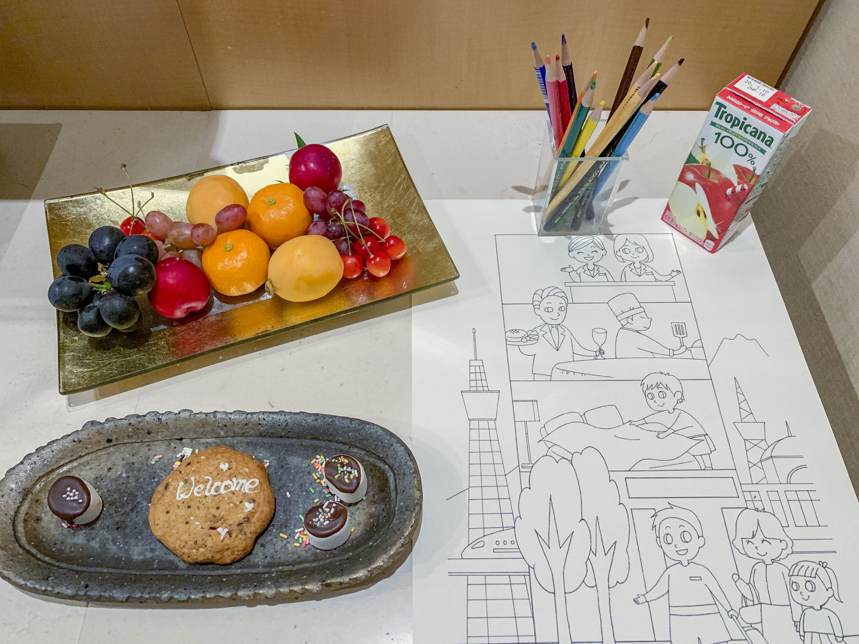 In-room welcome amenities of fruit in addition to a juice box and plate of sweets for kids next to colored pencils and a coloring sheet featuring Tokyo sights.