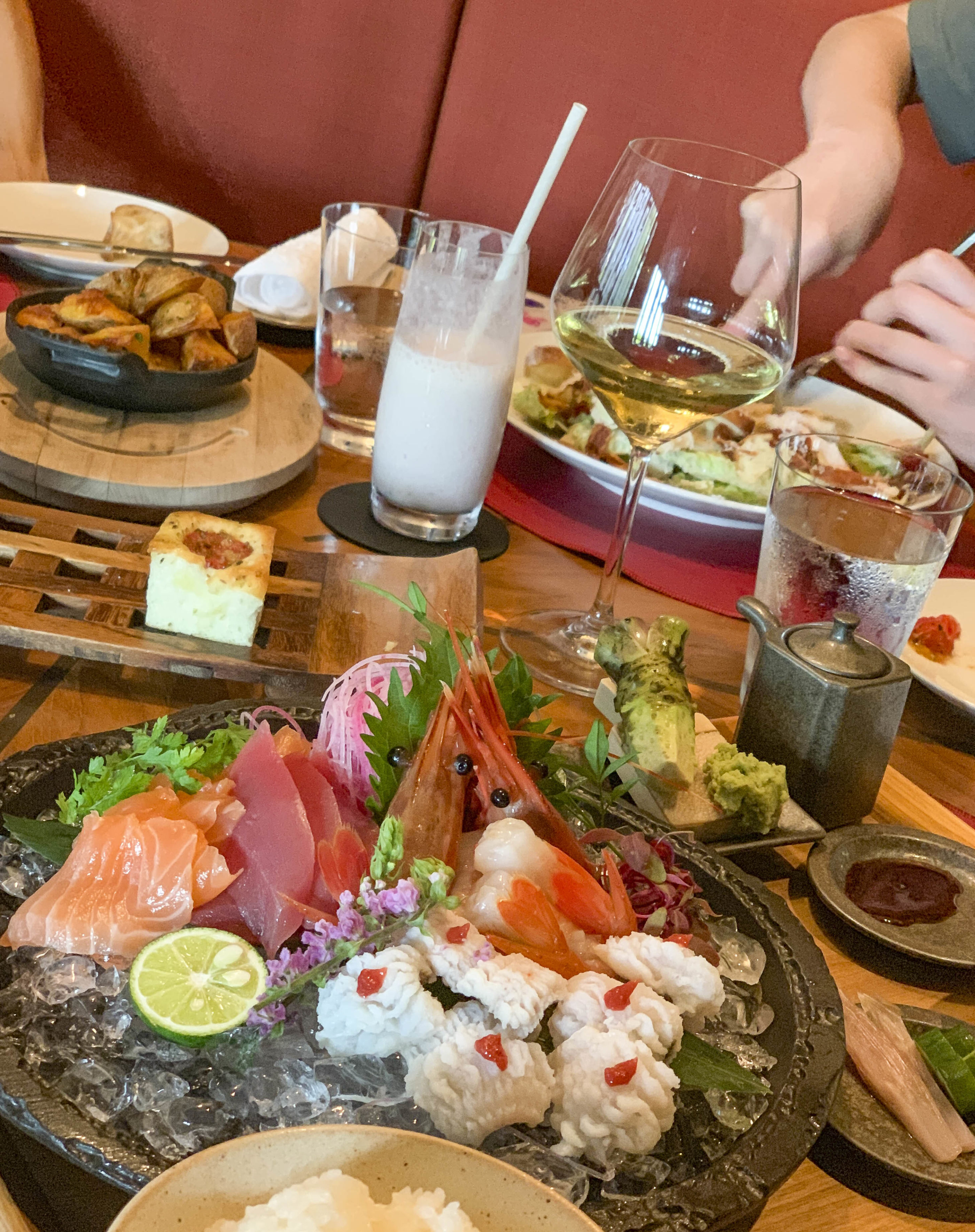 A platter of five types of fish on ice on the table with grate-your-own wasabi and fresh ginger.