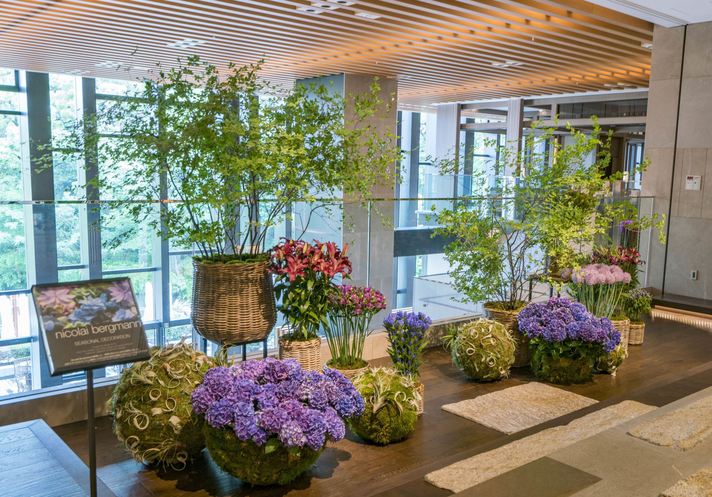 Moss orbs and spheres with flowers sit in front of baskets full of live arrangements in the lobby at Four Seasons Kyoto
