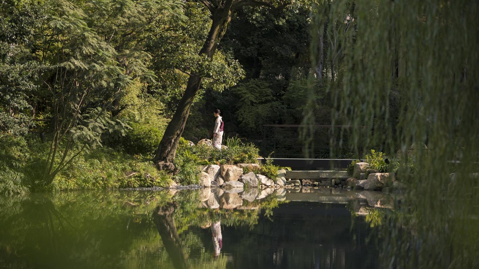 A woman in a kimono crosses a bridge over the pond in Shakusuien garden.