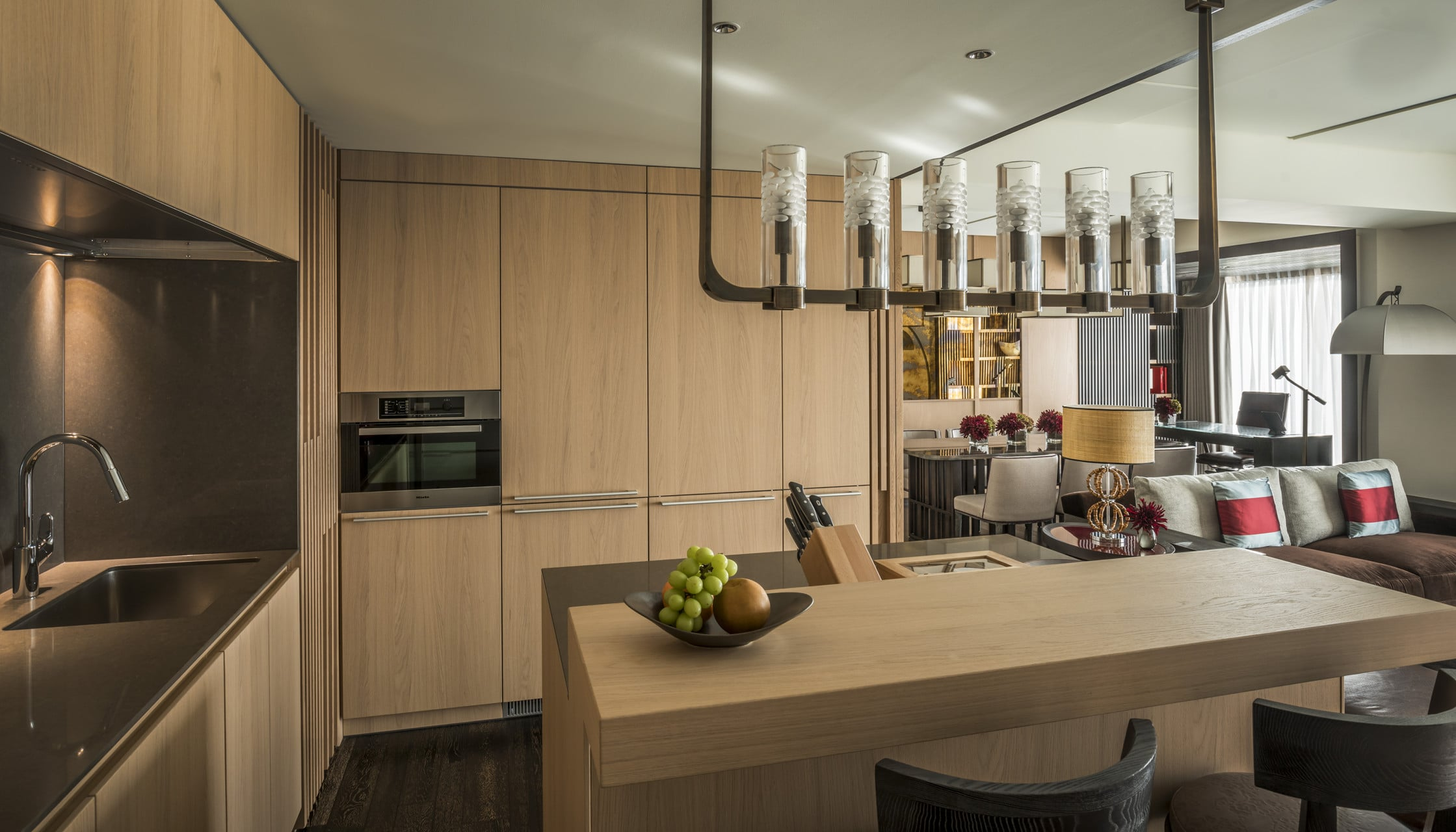Interior view over the light-colored wood panel kitchen and its kitchen island to the living area and dining room in a Residential Suite.