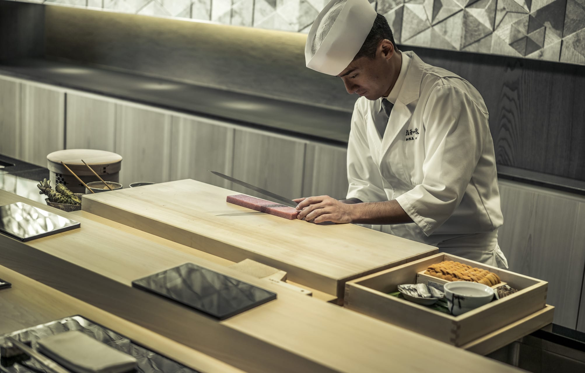 A sushi chef slices fish on a pristine wood chopping block with a long blade.