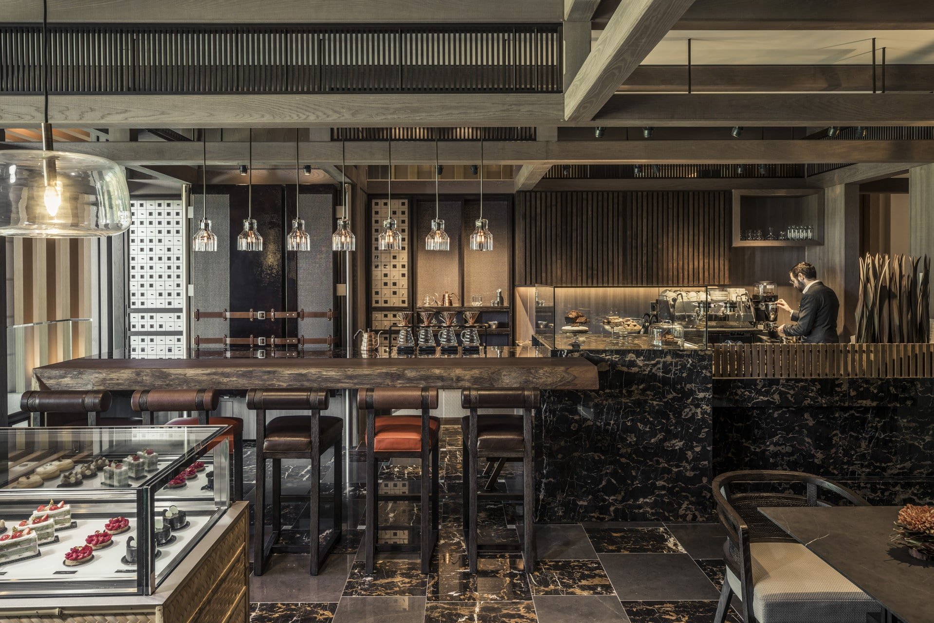 The dark, zen wood bar at The Lounge offers coffee and drinks but you can take desserts out of the adjacent glass case to-go.
