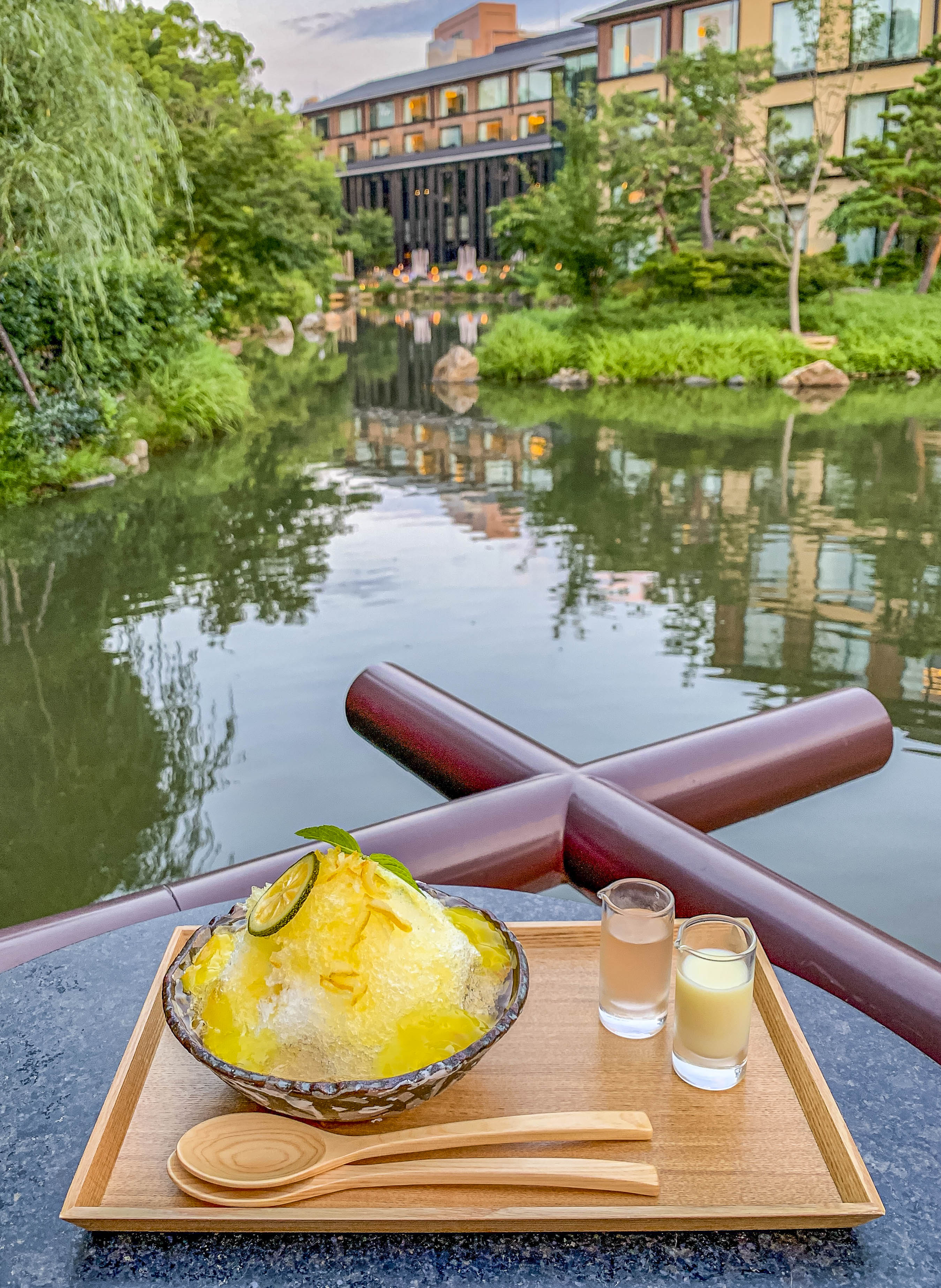 The giant Yuzu Citron shave ice in a bowl on a wood tray with a view of the pond and hotel in the background.
