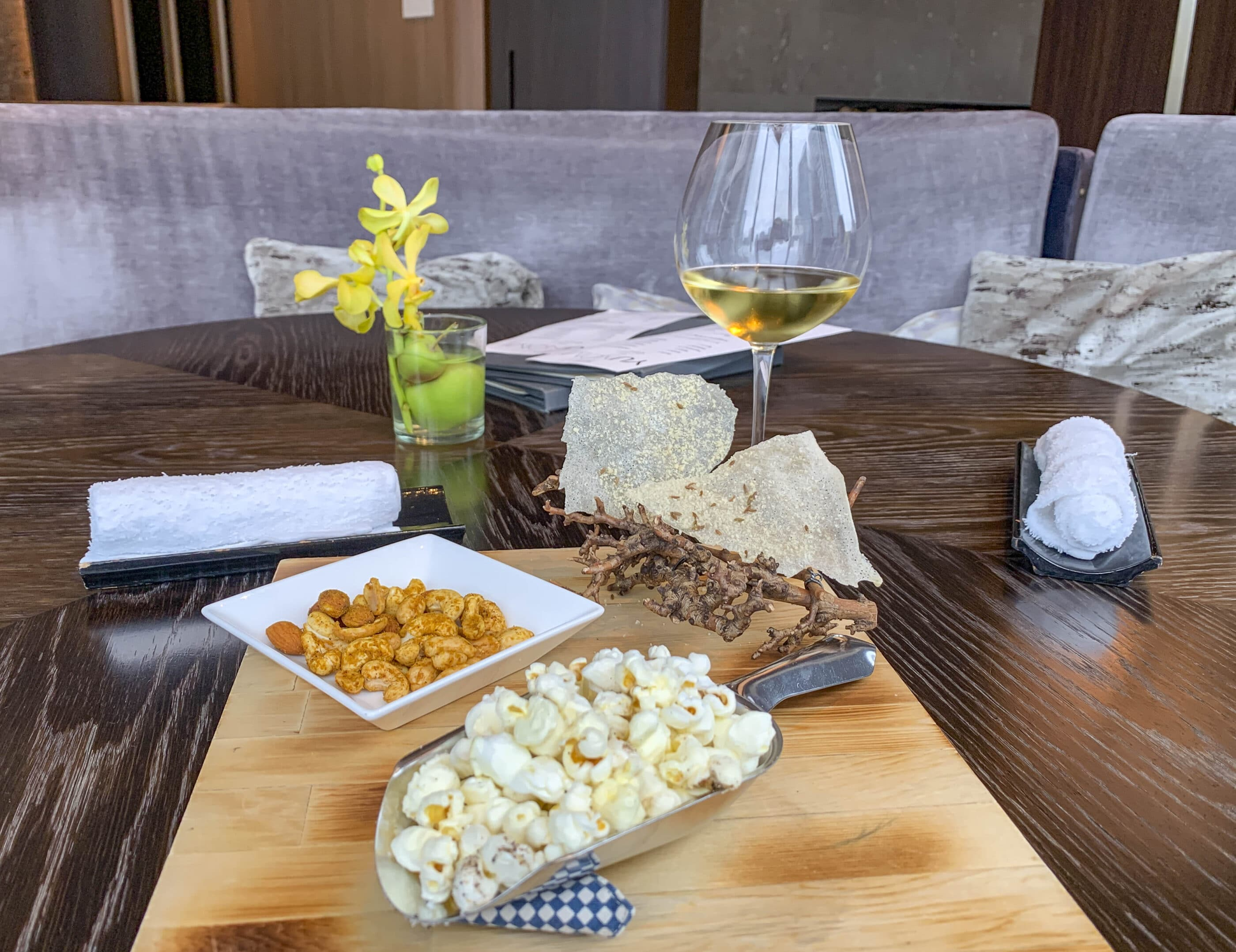 Beautifully plated bar snacks on a wooden board next to a glass of white wine in the Motif bar.