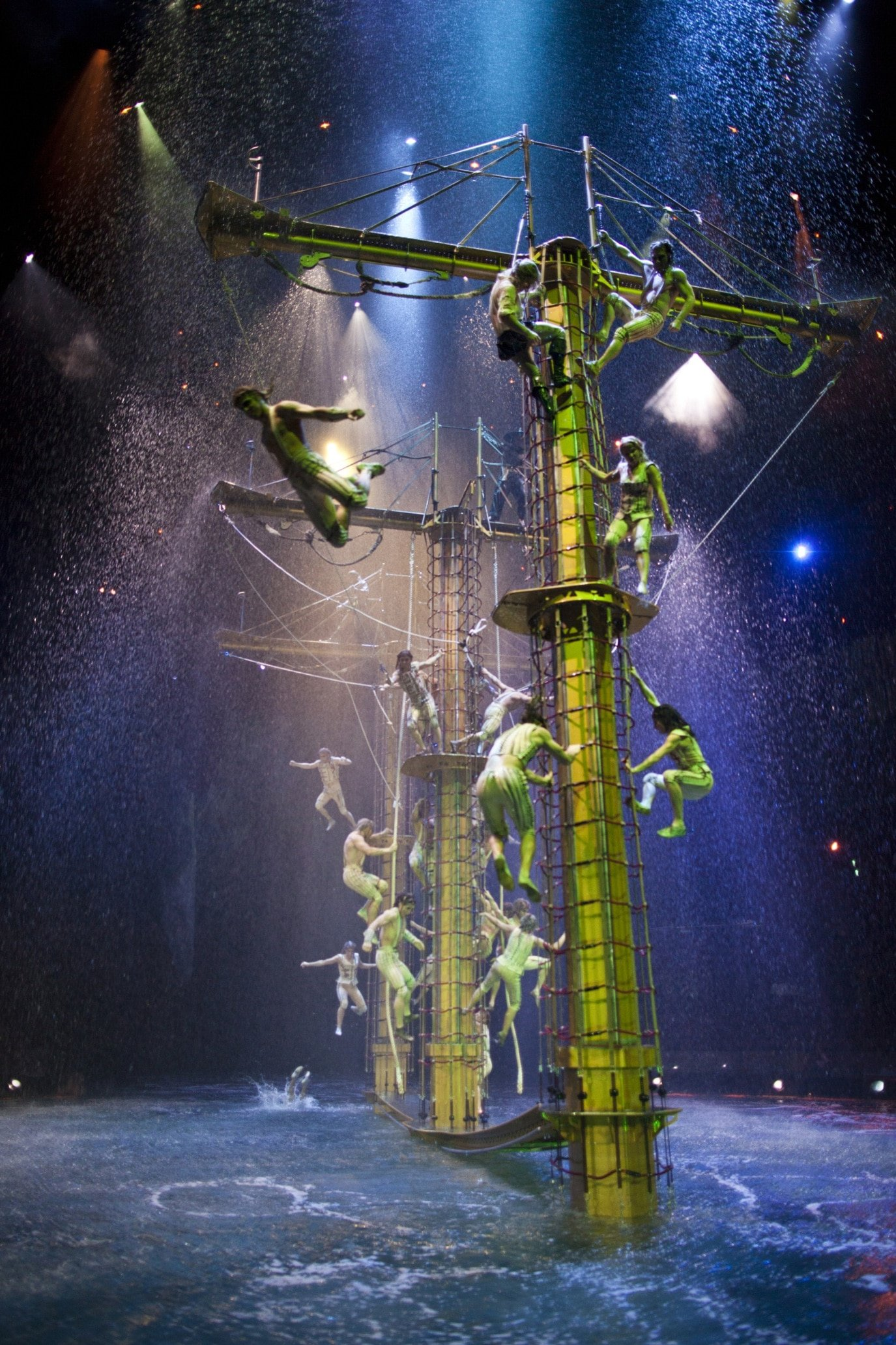 Acrobats climb up a shipwrecked ship  surrounded by water on stage.