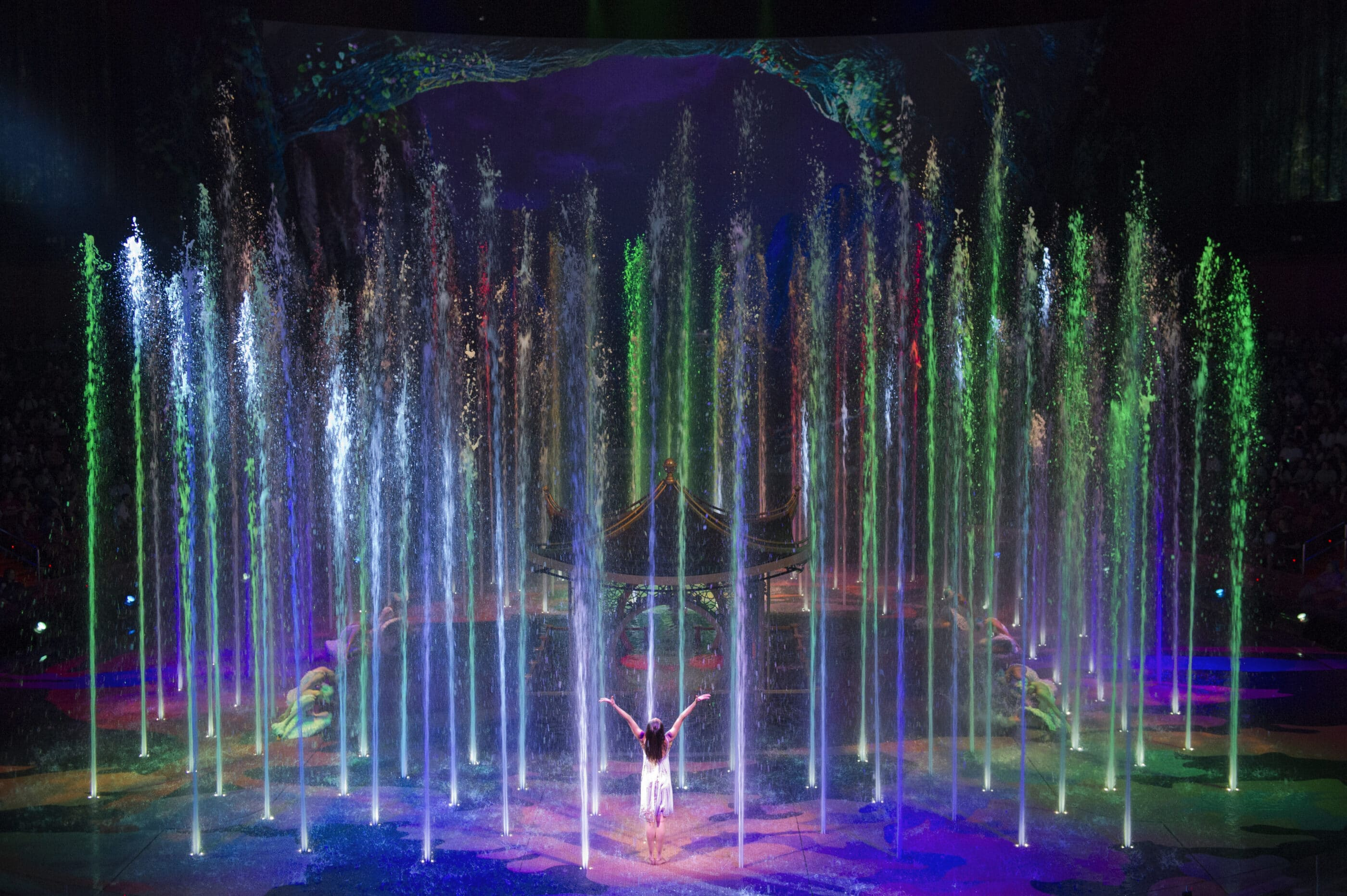 The princess with arms raised appearing to lift water high into the air on stage in front of the pagoda.