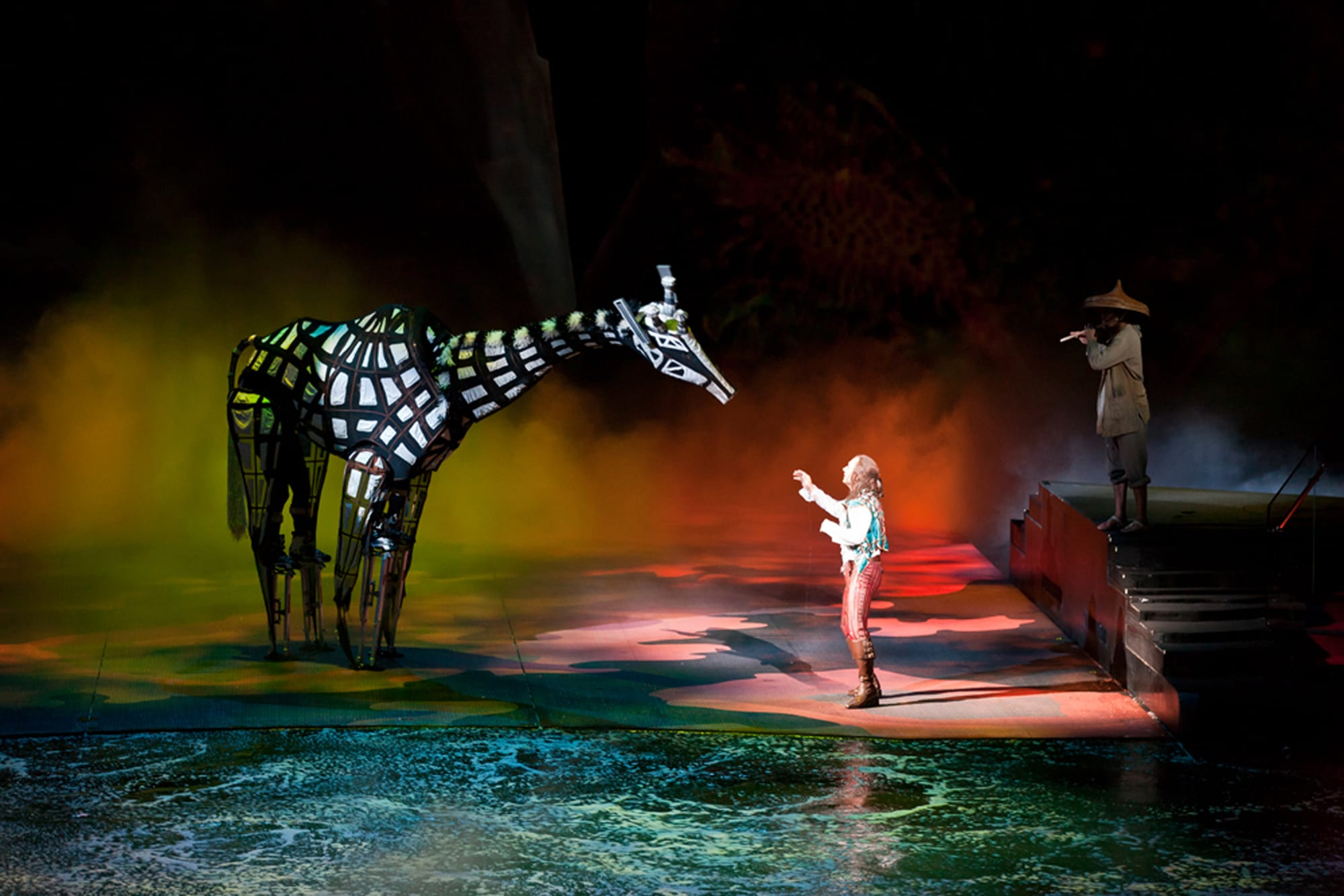 A mystic giraffe character and stranger on stage.