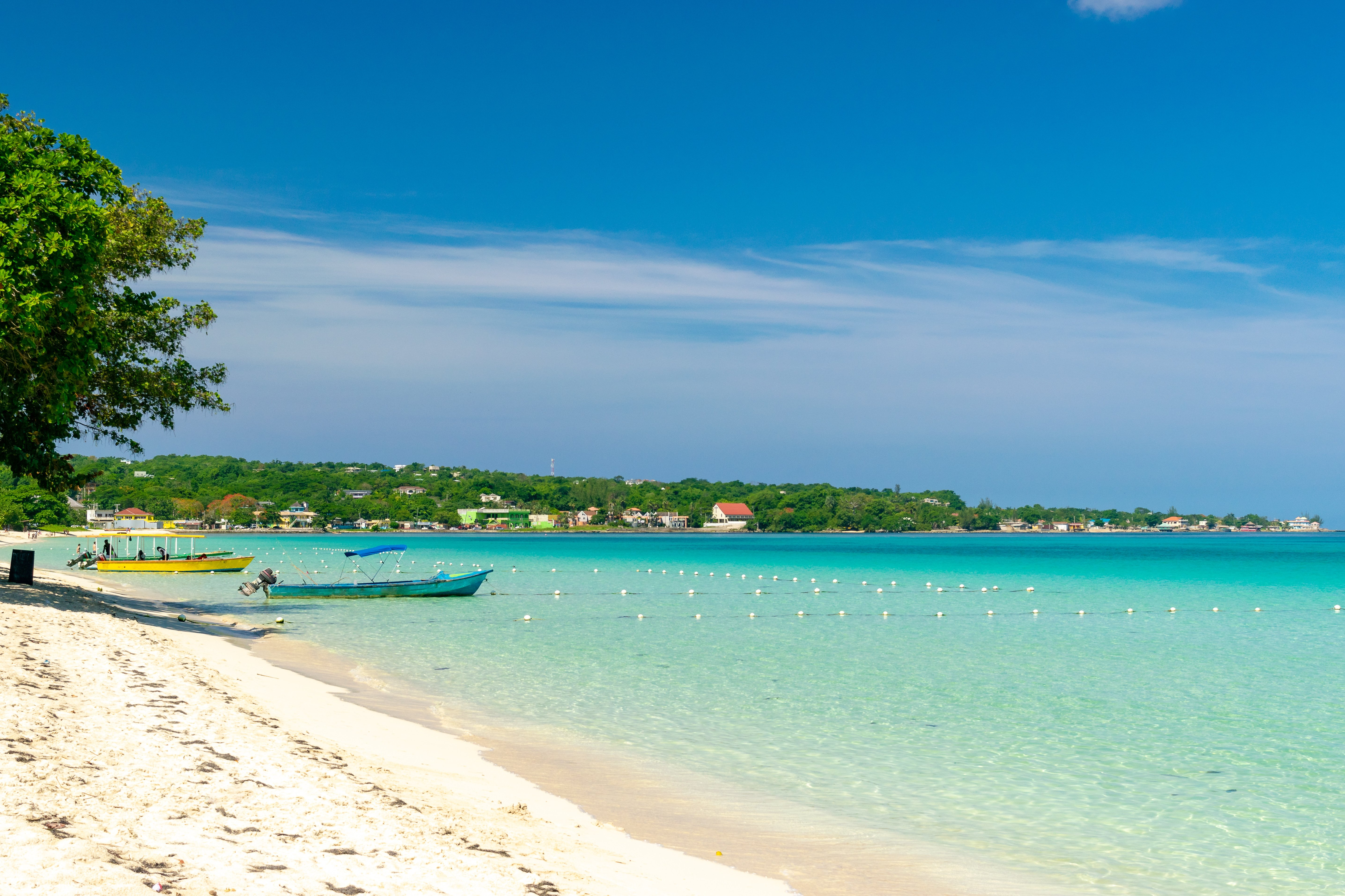Colorful boats docked in the sand of Seven Mile beach in Jamaica, bordered by stunning turquoise water.