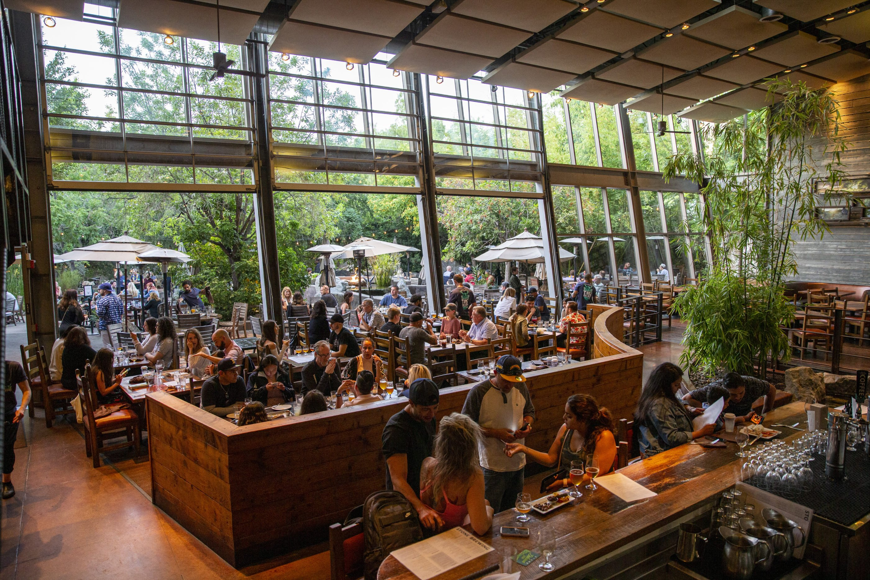People gathered at the bar and seated at indoor and outdoor tables on a busy day at Stone Brewing.