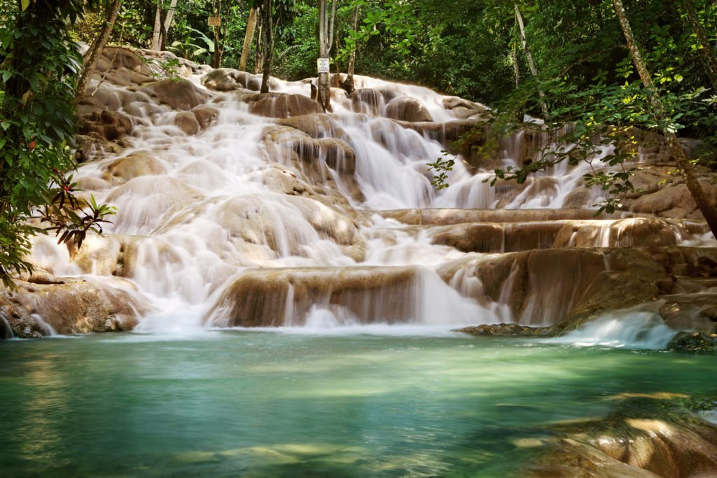 Dunn's River Falls flowing over rocks into a turquoise pool of water.