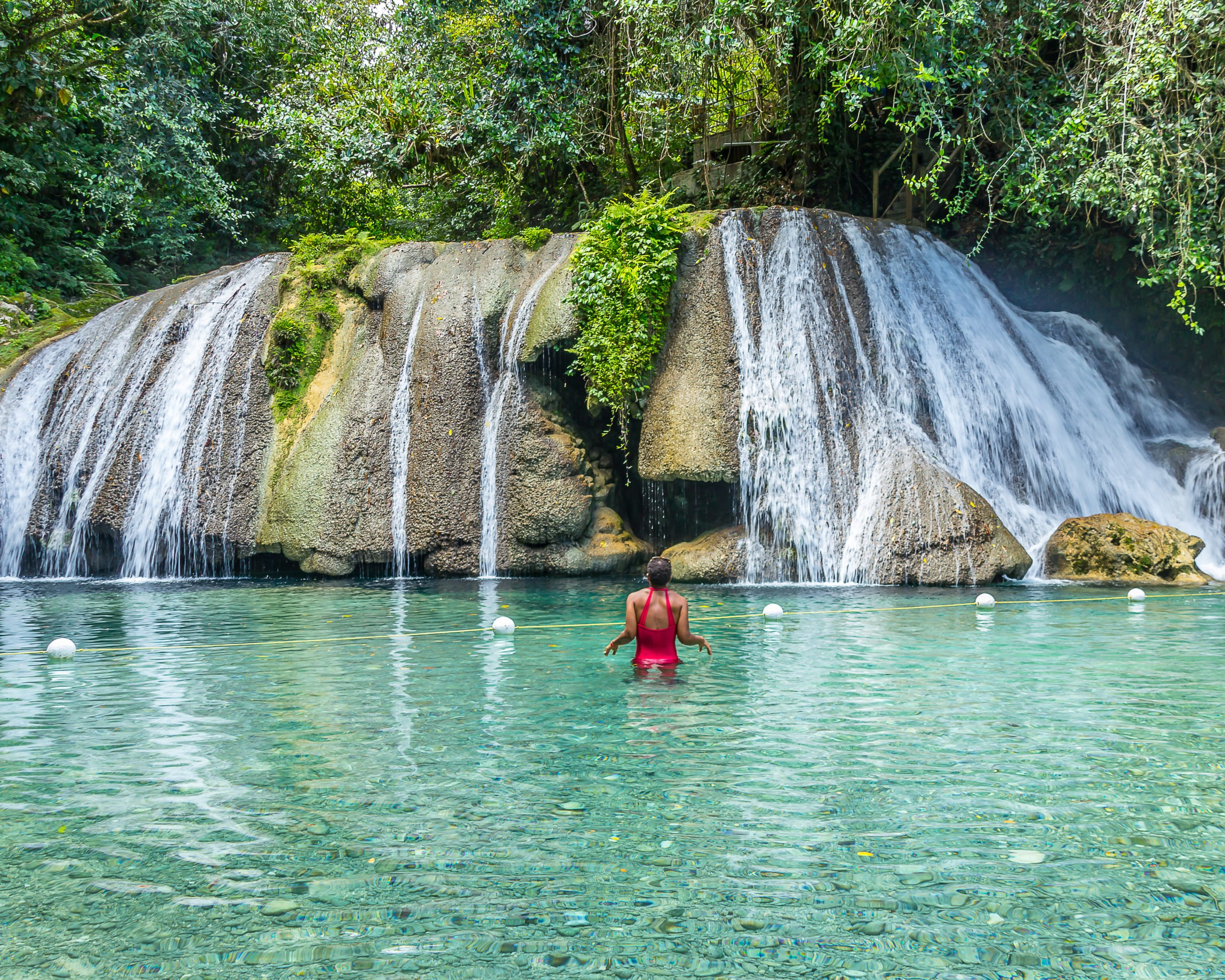 A woman in a red bathing suit wading in waist deep clear water faces Reach Falls.