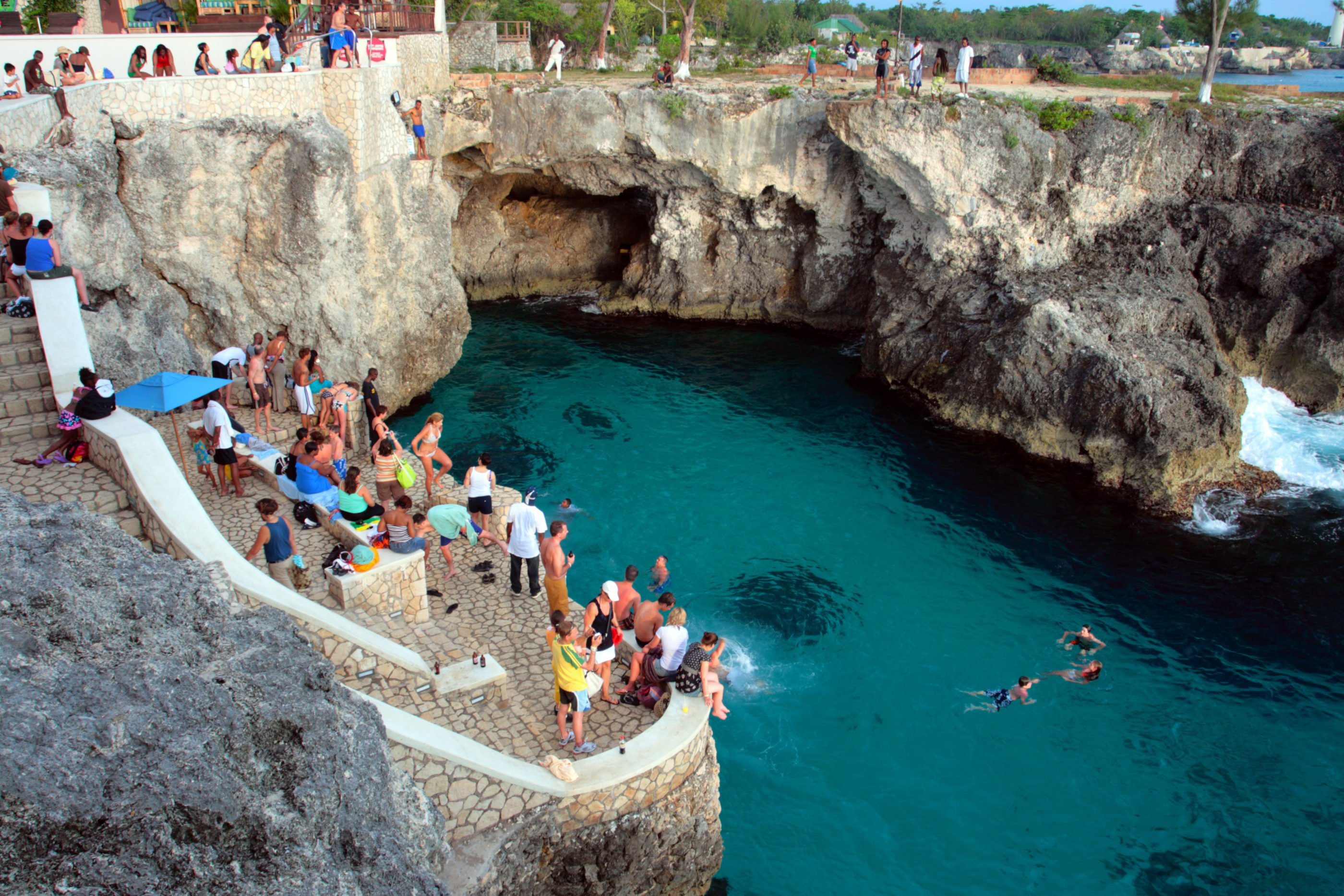 Aerial view of people watching others dive off of the famous cliff into the blue water at Rick's Cafe.