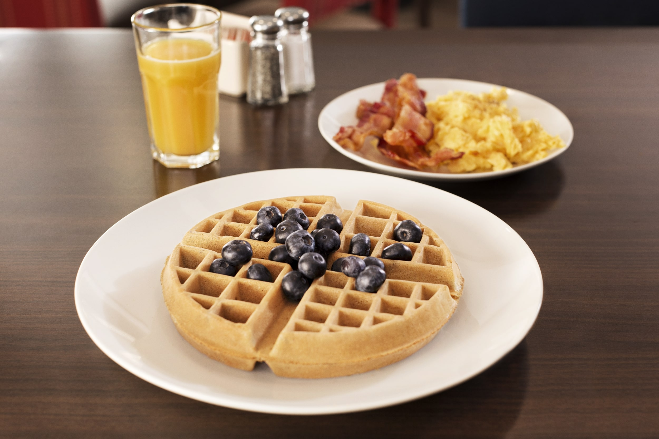 A plate of waffles next to a plate of eggs and bacon with glass of orange juice.