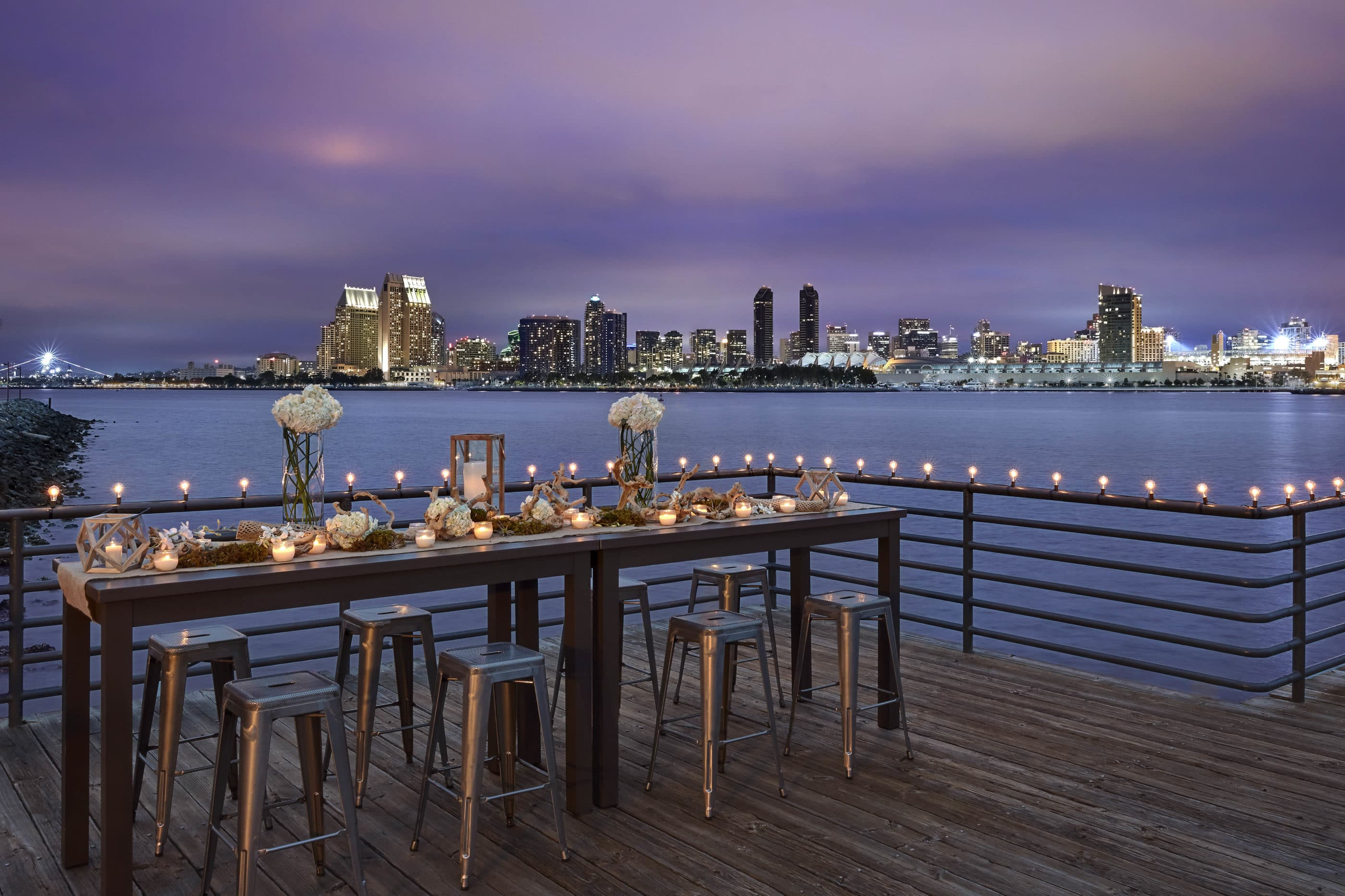 A decorated table with barstools on a patio with a view to downtown San Diego at dusk.