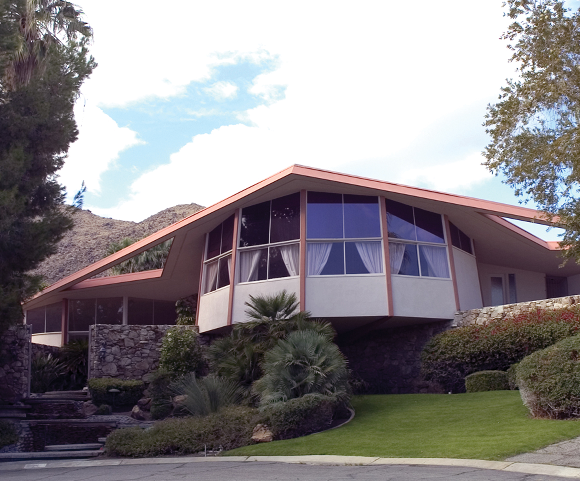The mid-century exterior has big, rounded windows with drawn curtains and a space-age looking roof.