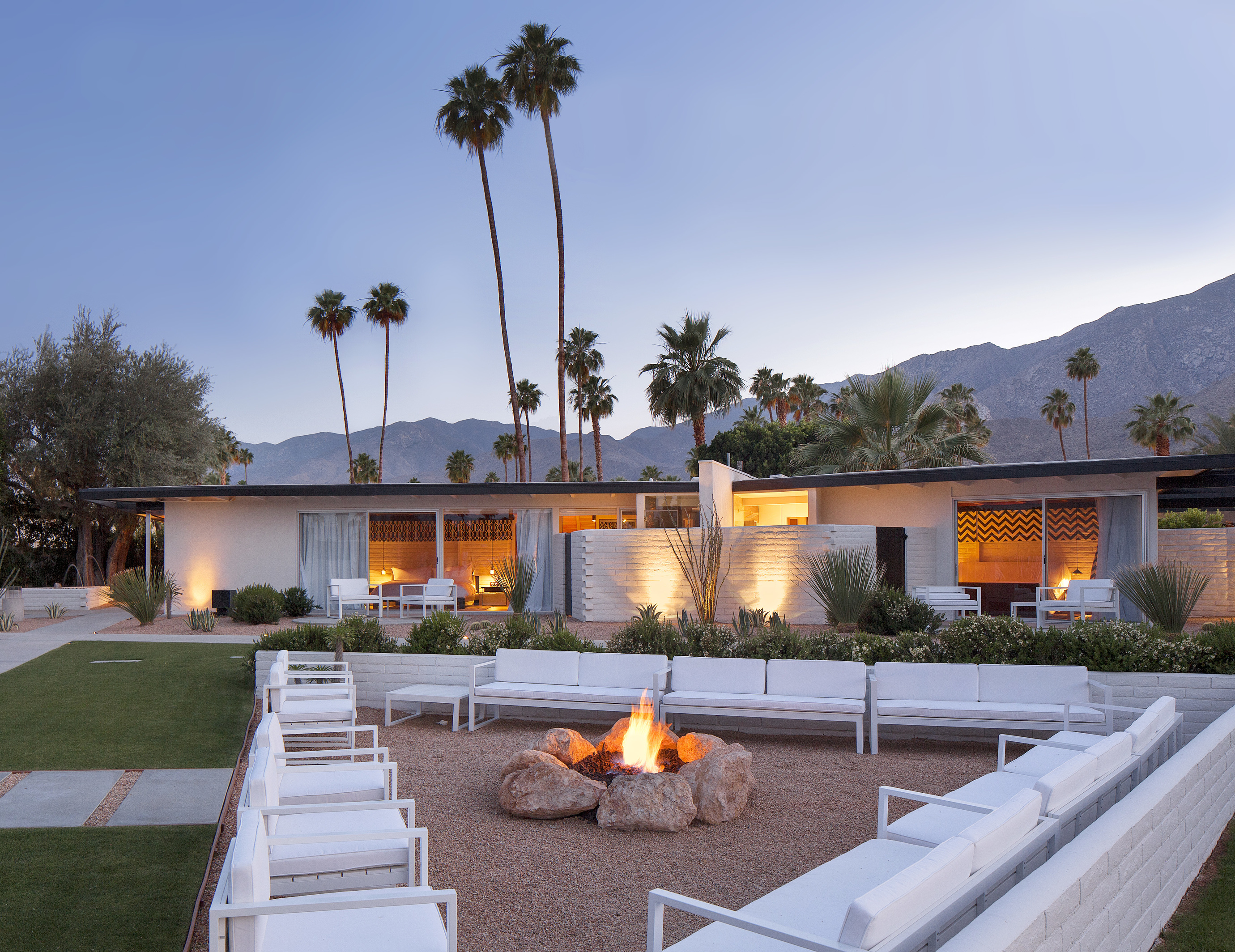 Modern white outdoor lounge chairs in a triangle configuration surround a rock fire pit with the one-story accommodations in the background.