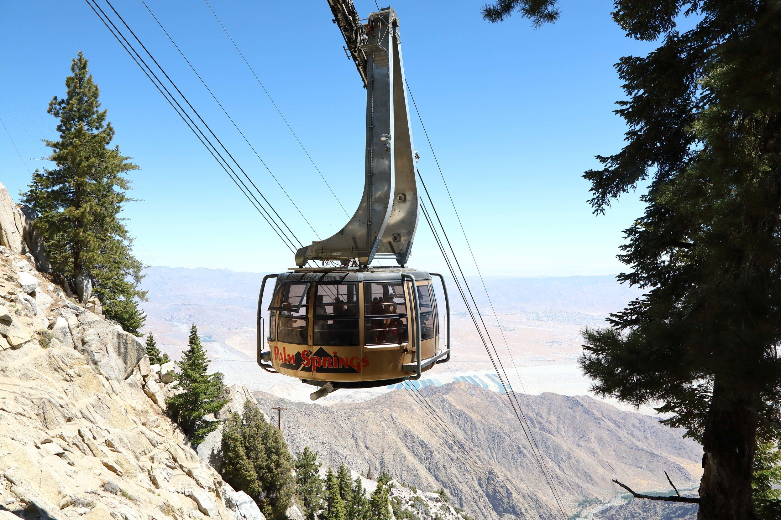 An enclosed tram moves guests downhill through the mountains.