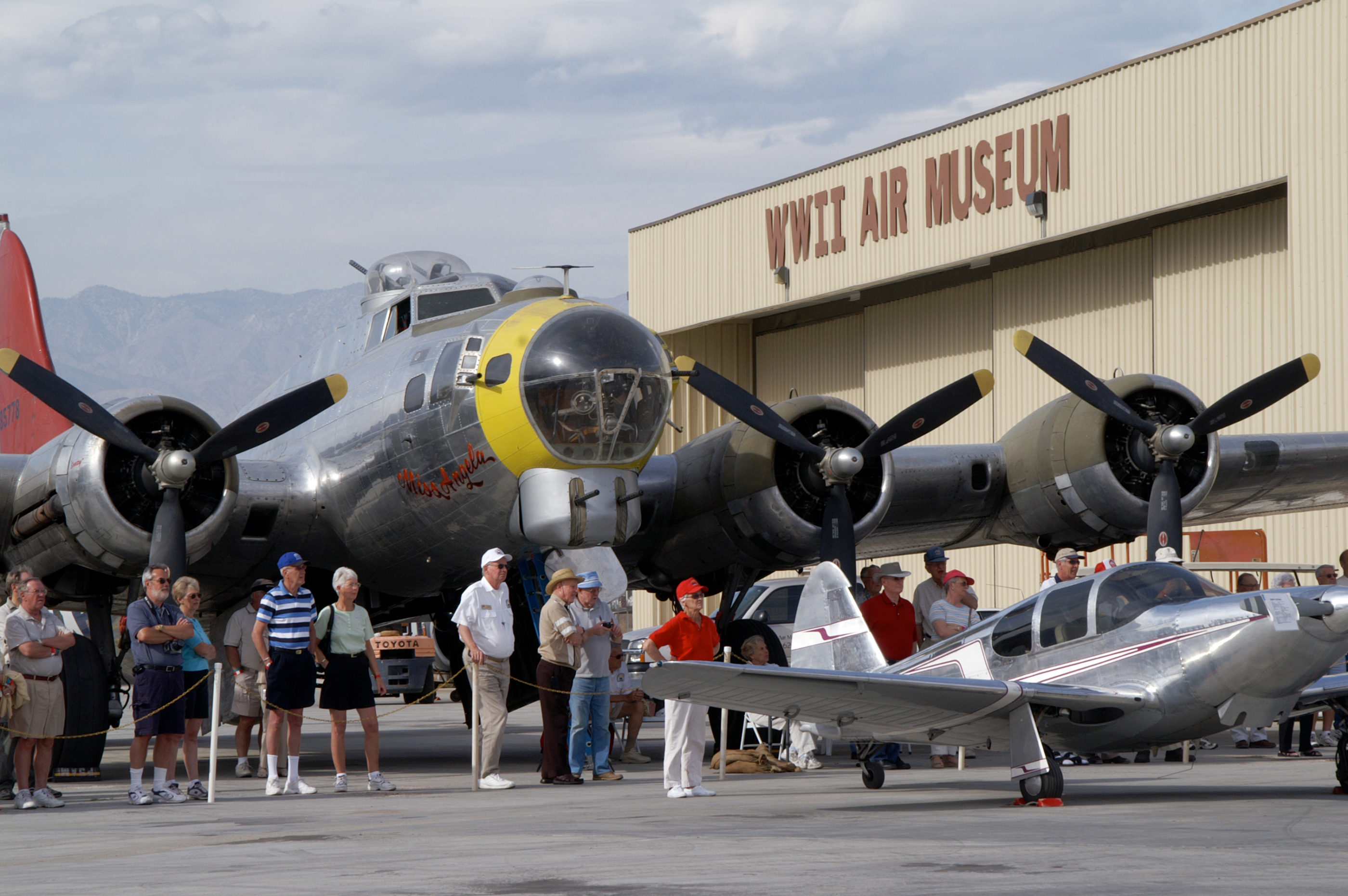 Guests stand outside under a large vintage aircraft.