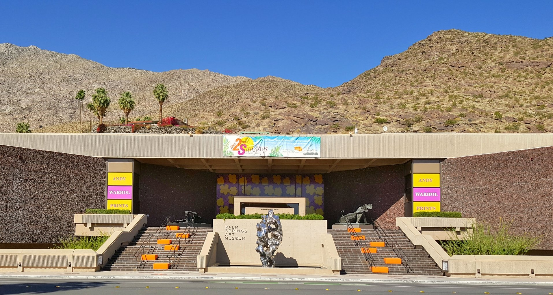 The one-story exterior of the museum with mountains and palm trees in the background.