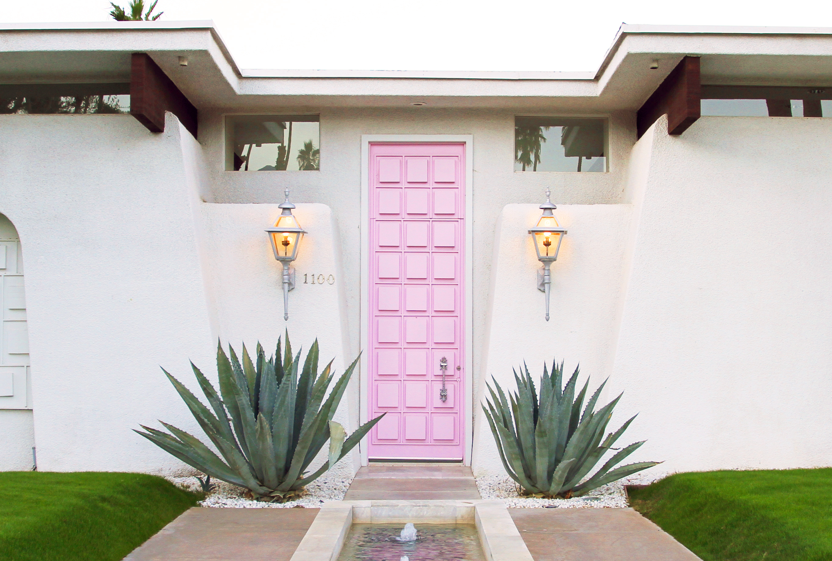 The famous cotton candy pink, narrow front door on a white one-story mid-century home, flanked by two agave succulents.