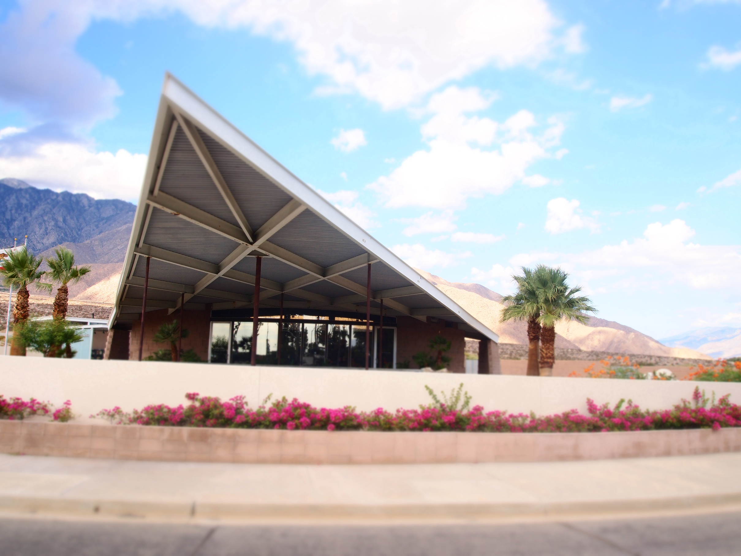 The triangular roof/overhang of the Visitor's Center juts into the sky. Mountains and palm trees are in the background.