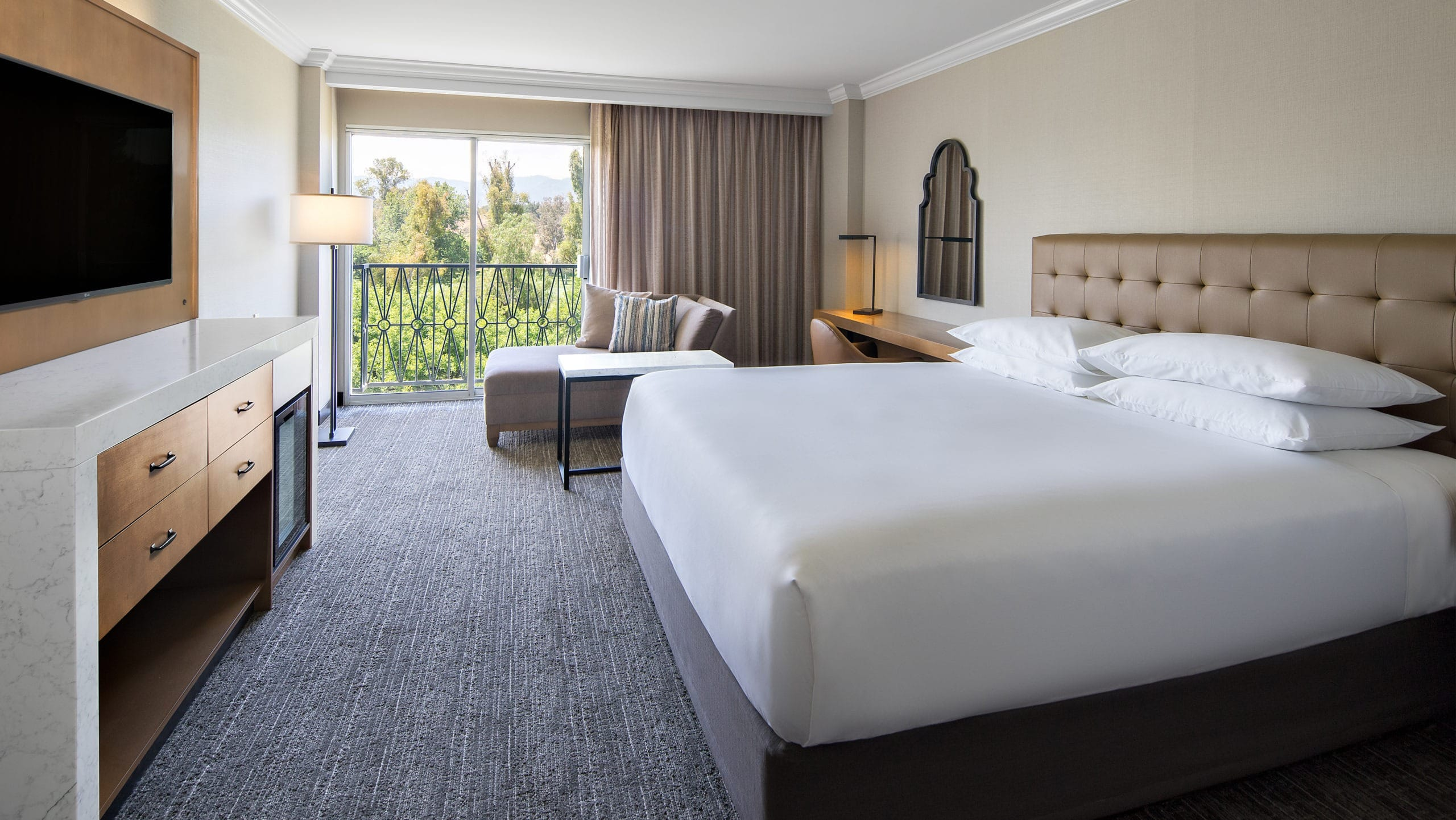 The contemporary interior with grey and neutral decor of a king room at Hyatt Regency Valencia.