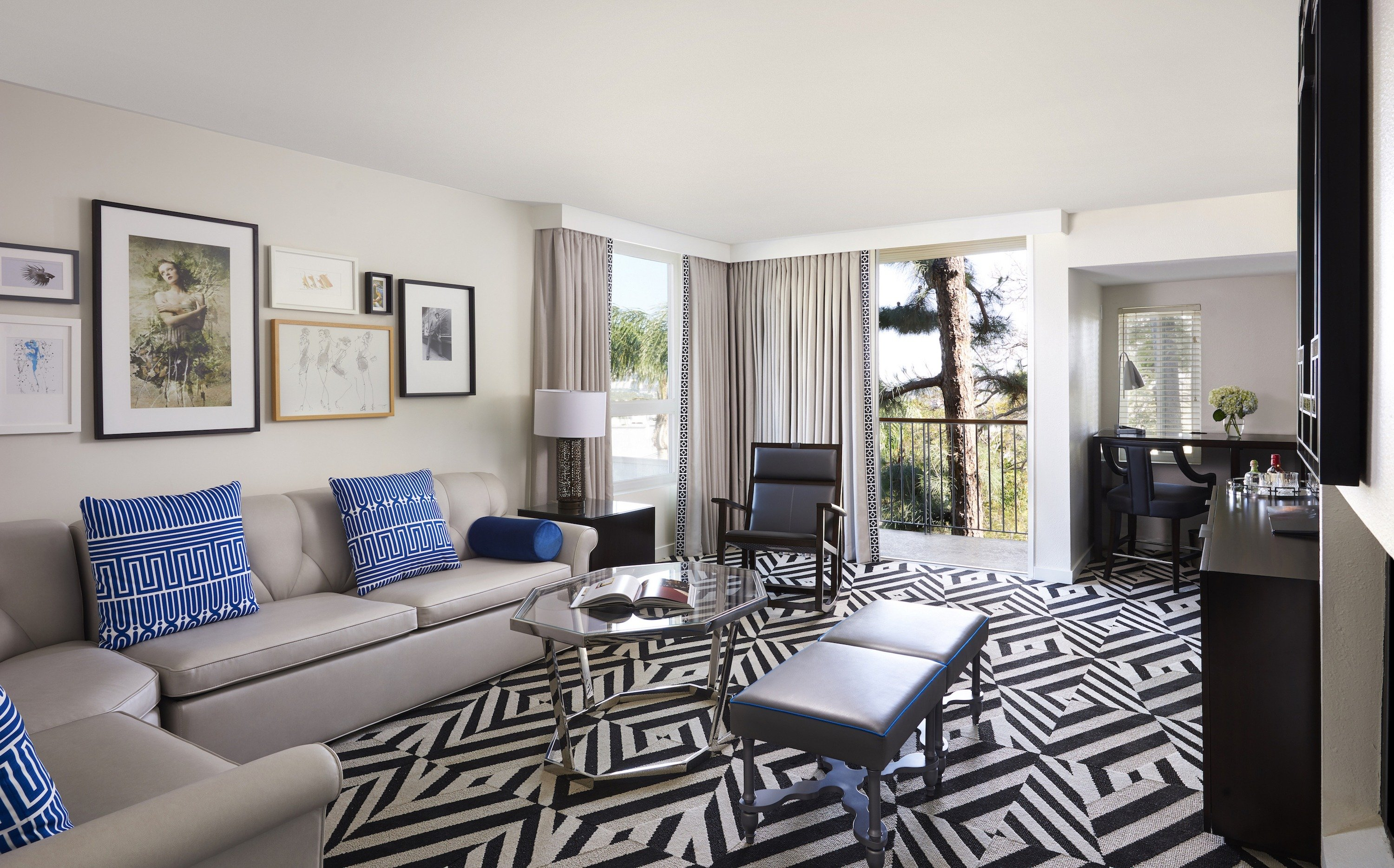 The living room of a one bedroom suite with black and white flooring and neutral decor with blue accents.