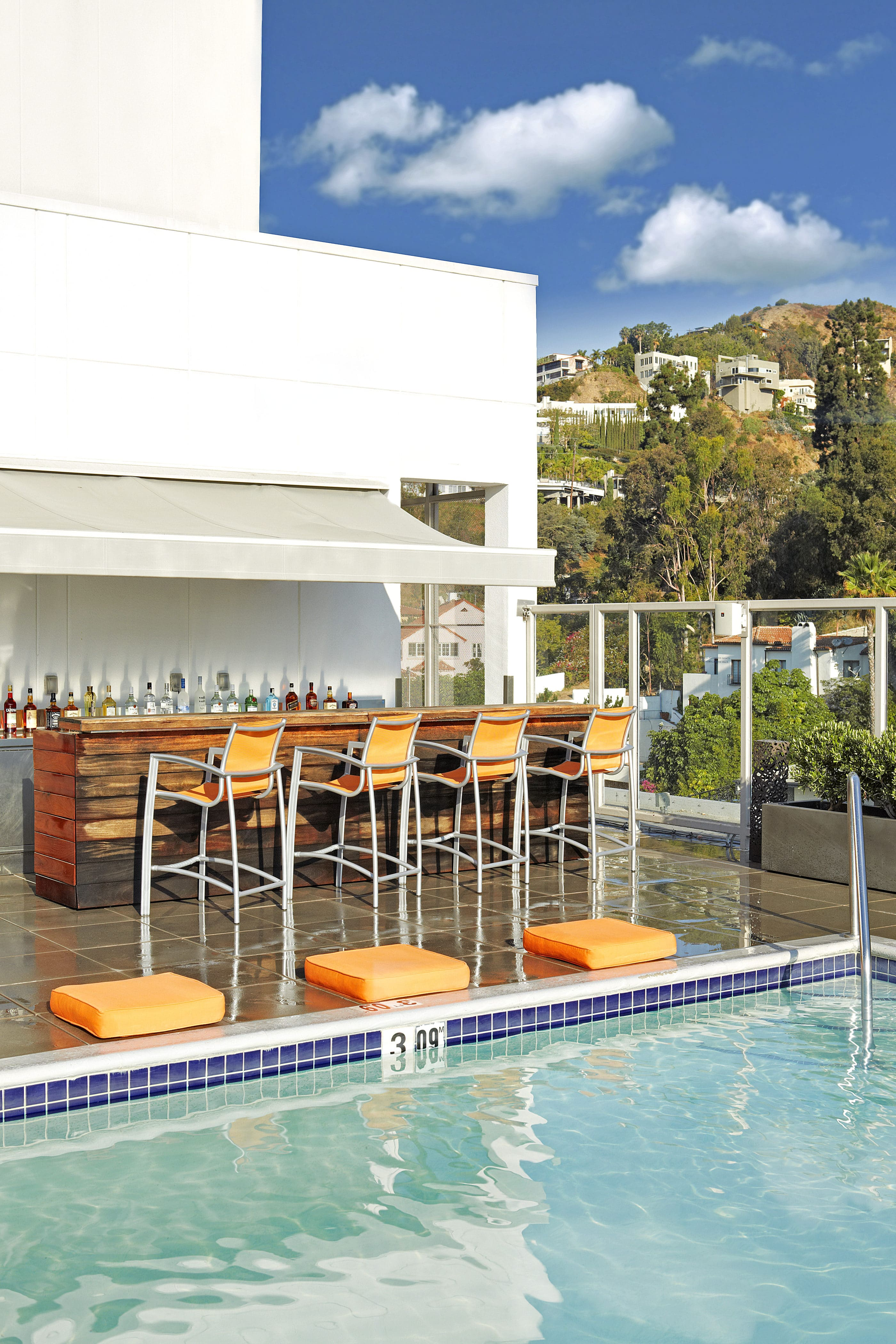 The chic pool bar with orange barstool chairs near the water's edge.