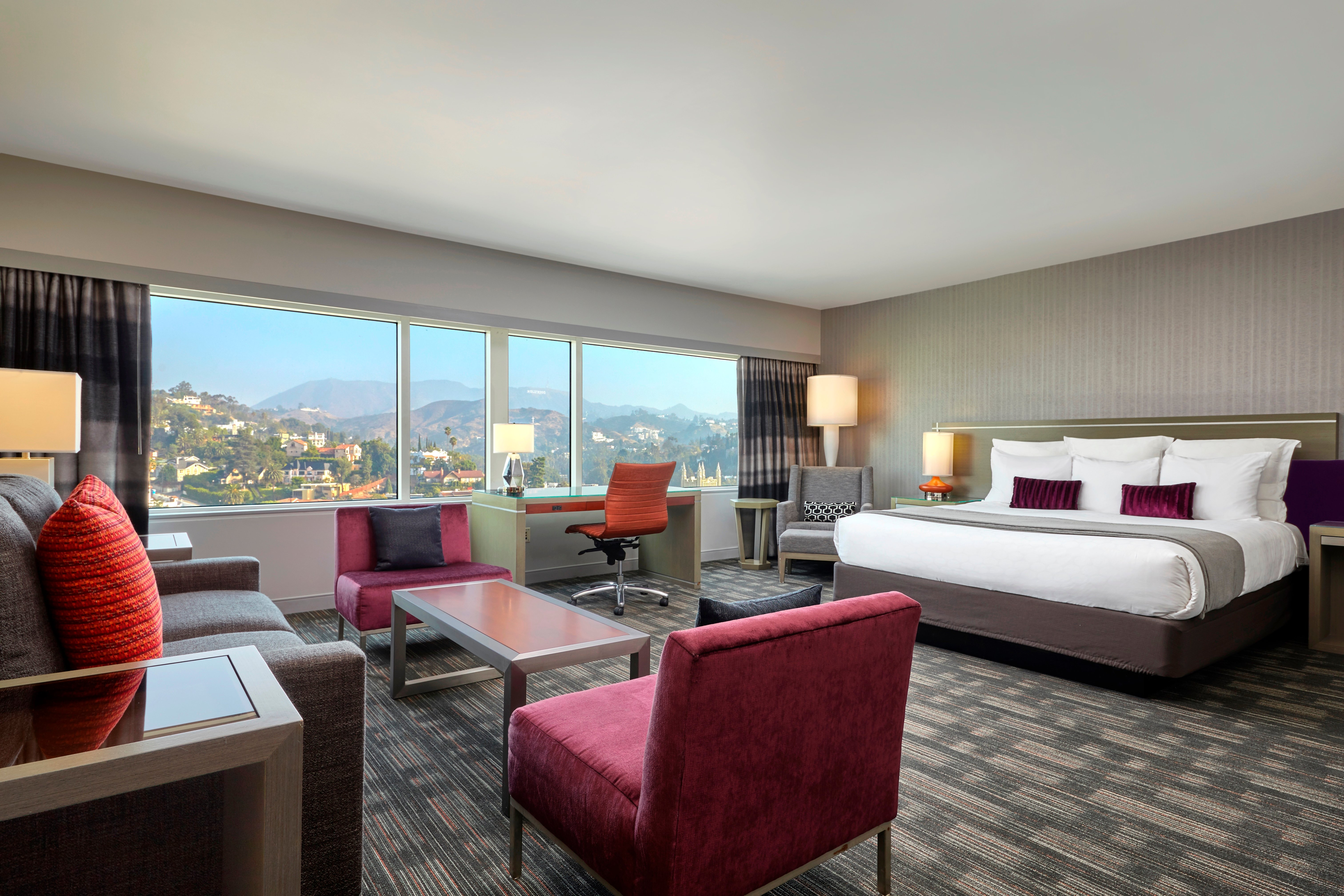 A large king room with grey tones and red accents that overlooks the famous Hollywood sign