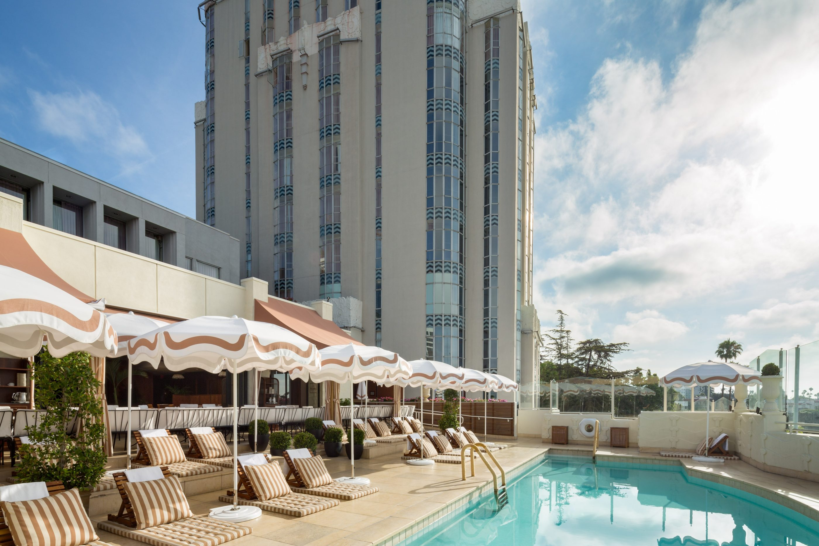 The outdoor pool deck on a sunny day surrounded by beige and white striped lounge chairs and umbrellas.