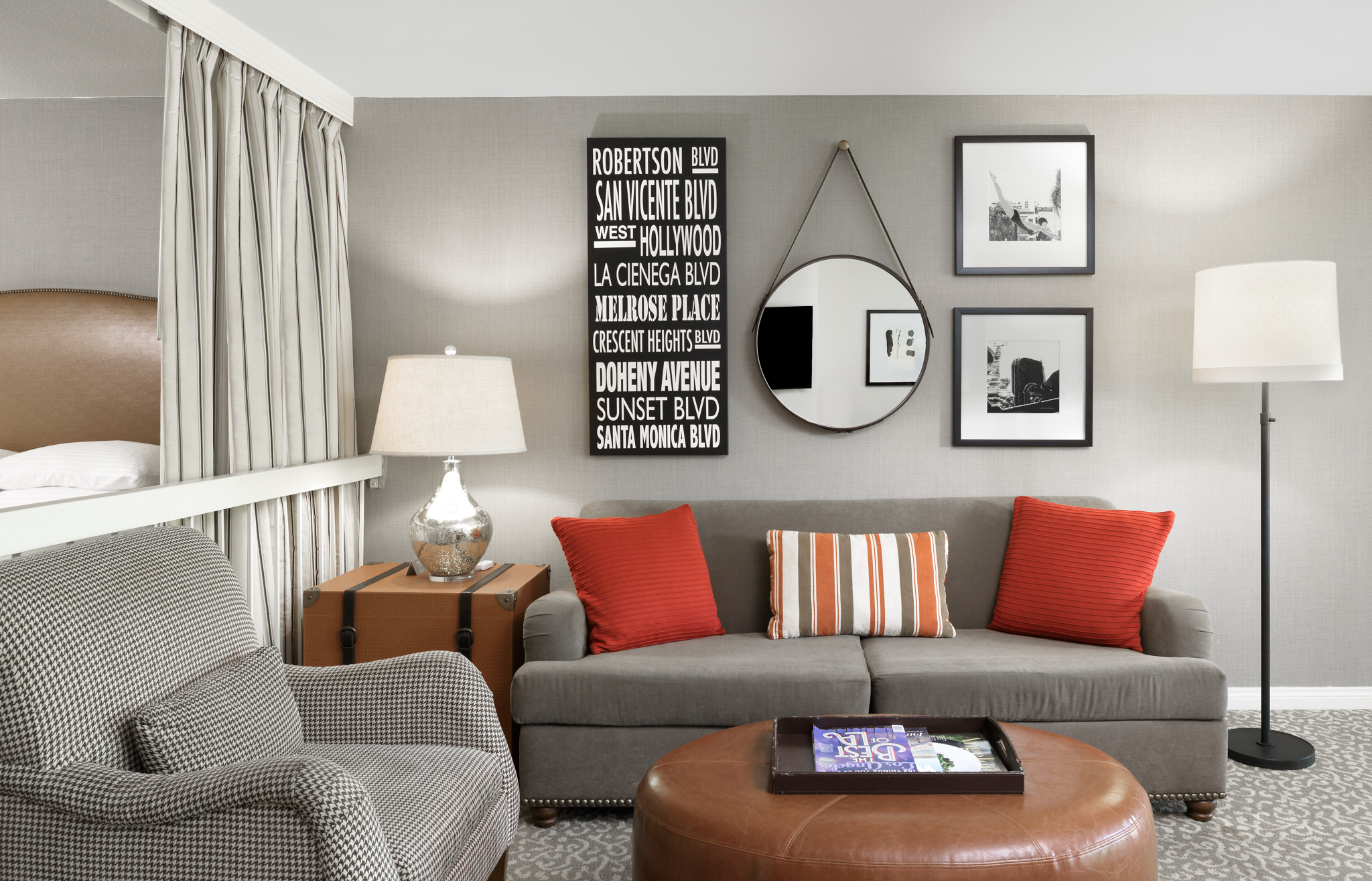 A suite living room with grey seating, orange throw pillows.