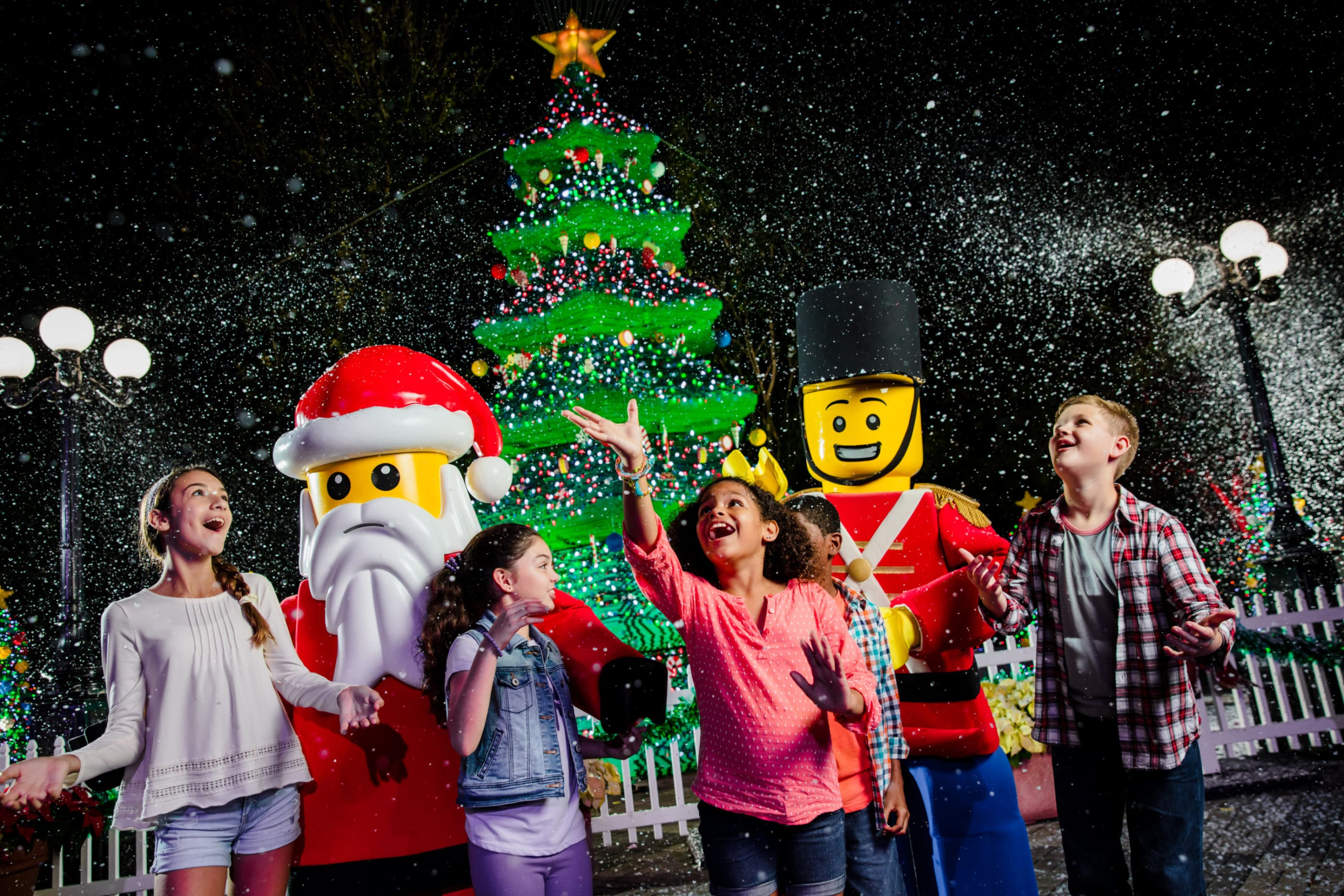 Kids stand next to LEGO Santa in front of the LEGO Christmas tree at night.