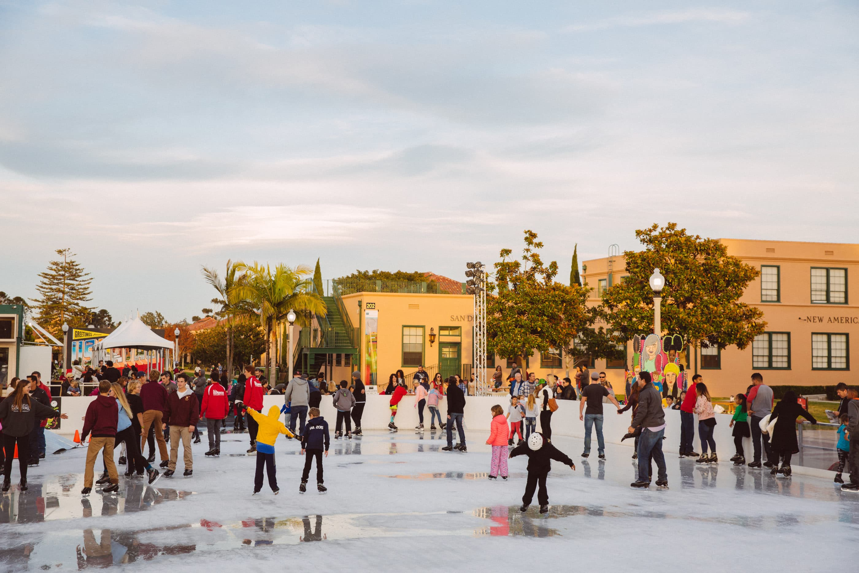 People ice skating at Liberty Station on a sunny day.