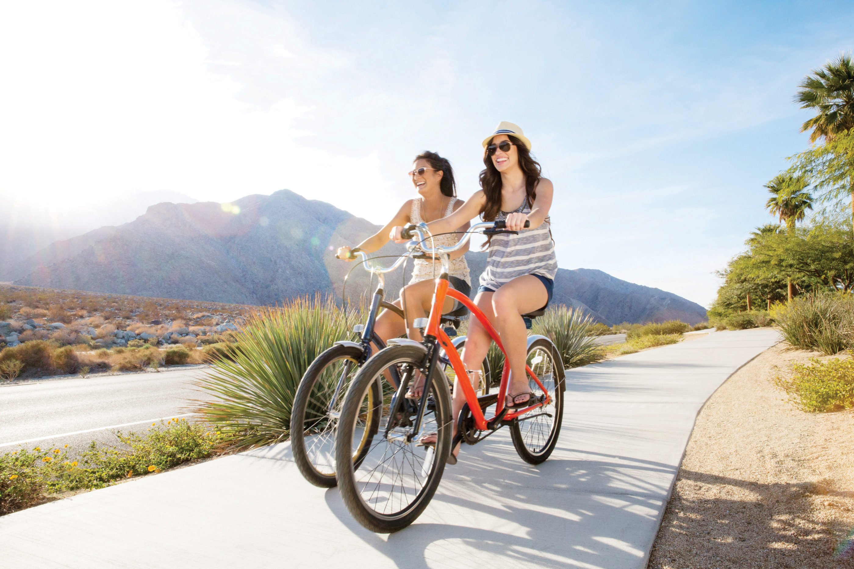 Two women ride bikes casually along a cement path with mountains and desert in the background.