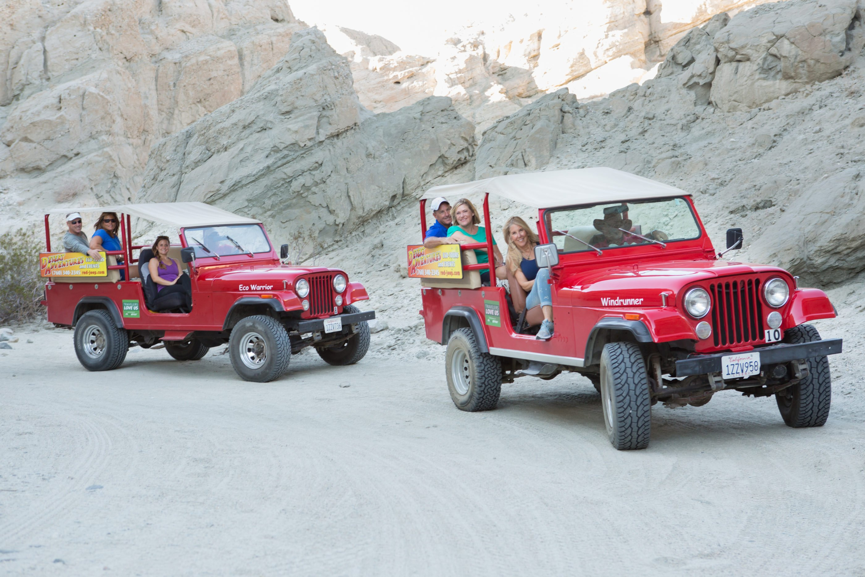 Two red Jeeps full of guests off-road in the desert.