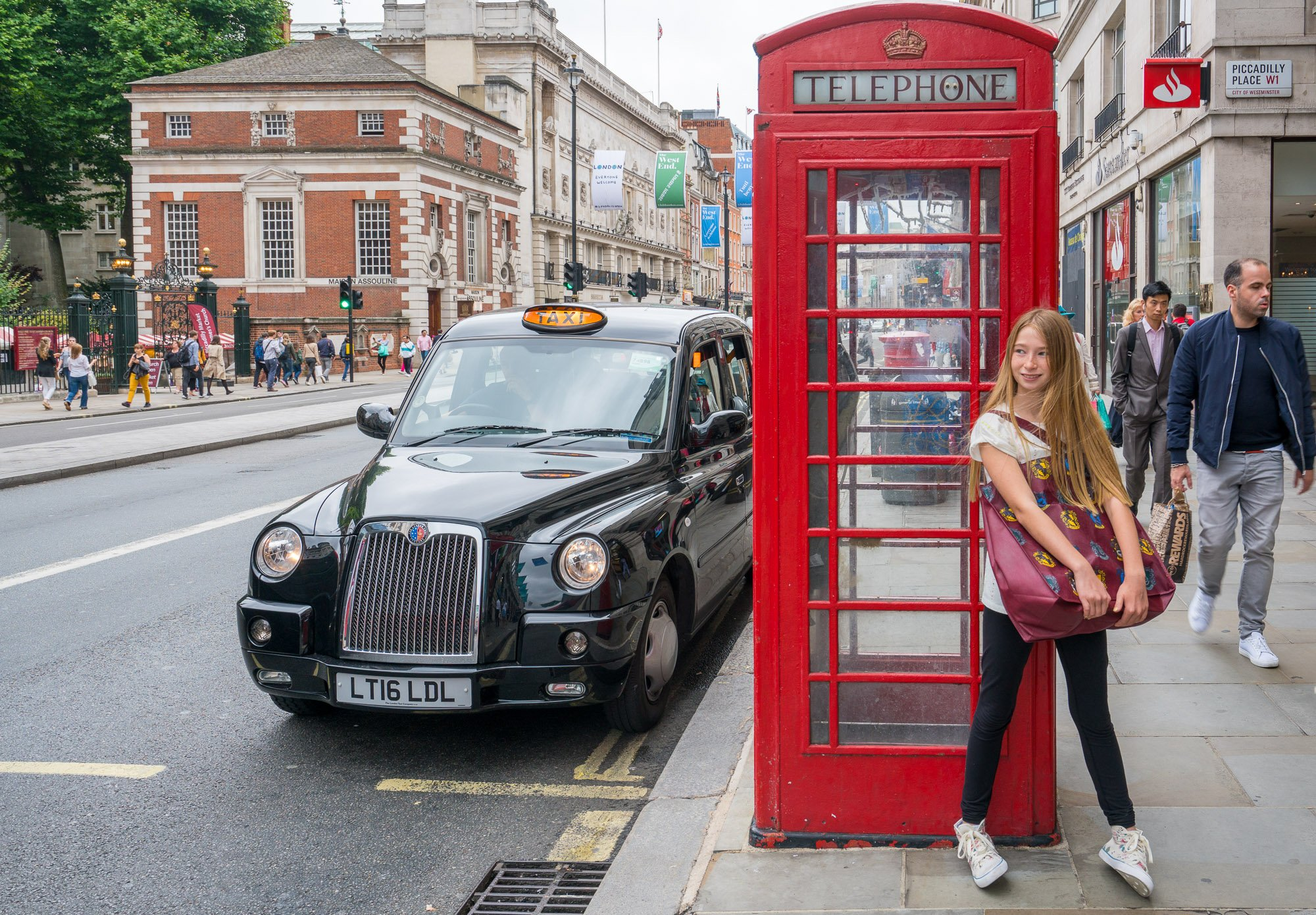Girl in front of a red British phone booth as a traditional black taxi passes by.