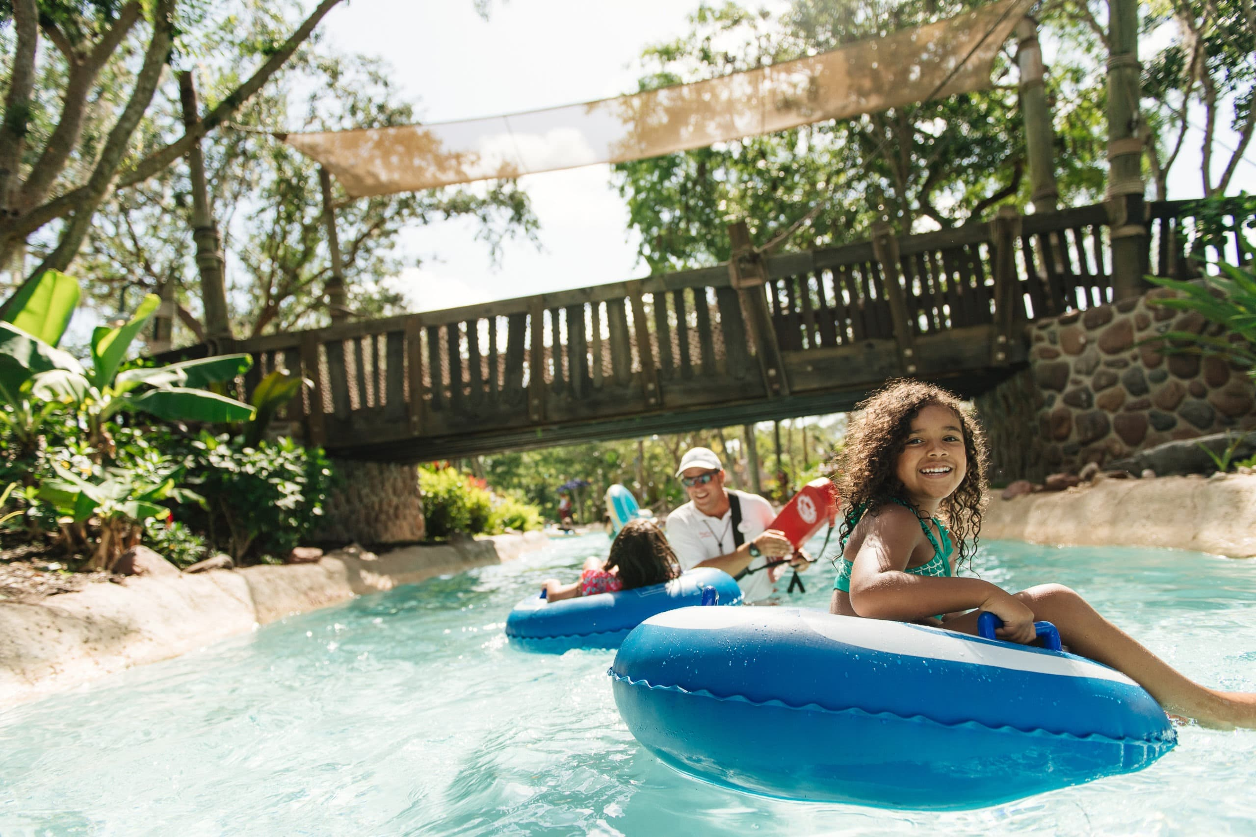 Two little girls float pass a lifeguard in the lazy river at Ketchakiddee Creek at Disney's