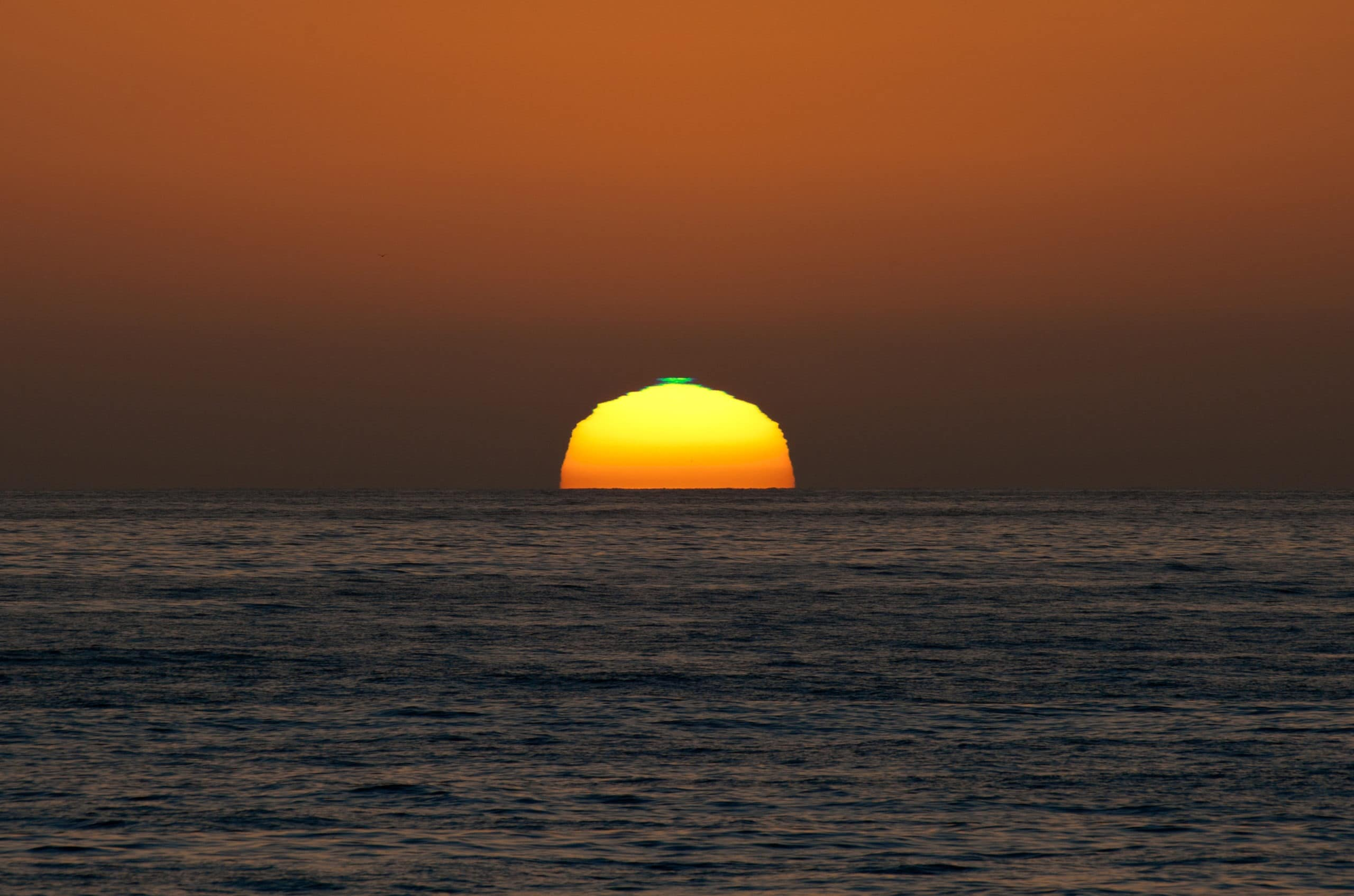 A sun setting below the ocean horizon with a small green line on top... the green flash.