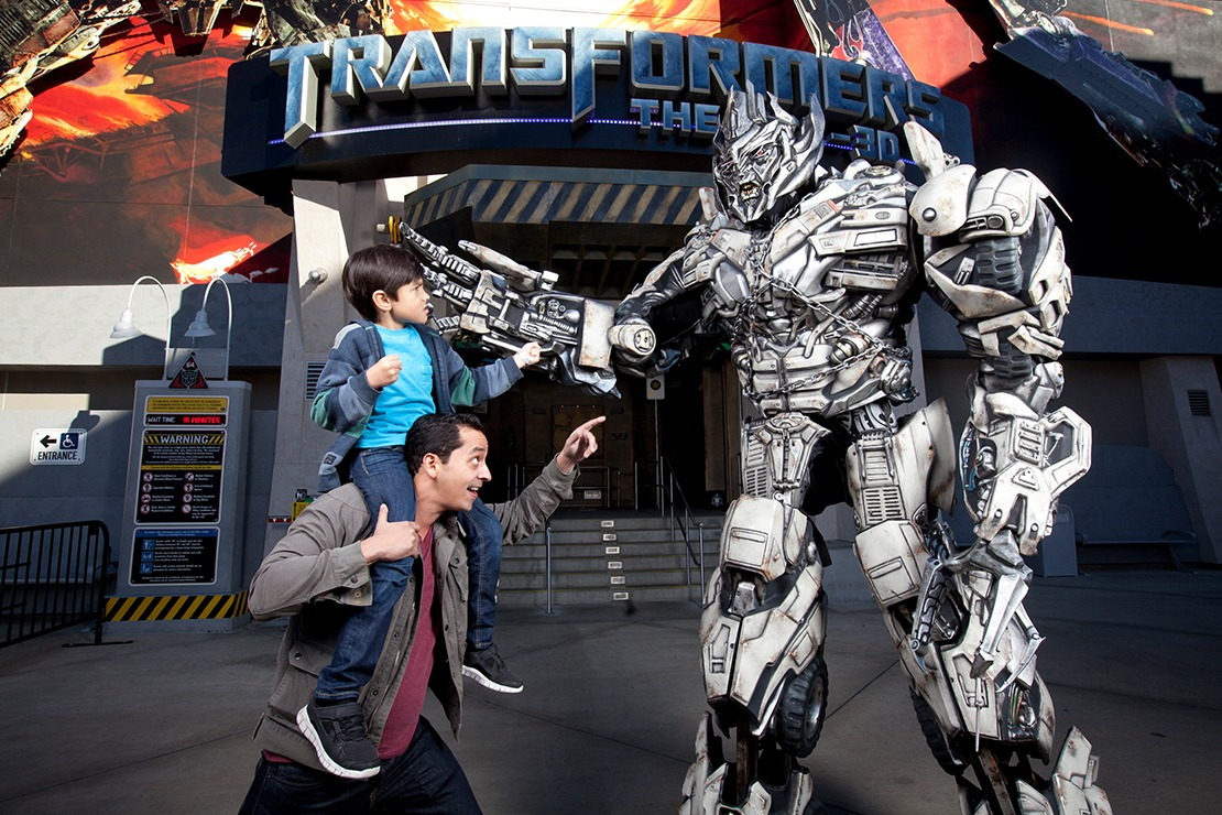 A boy on a man's shoulders points his finver at Optimus Prime in front of the Transformers Ride entrance at Universal Studios Hollywood.