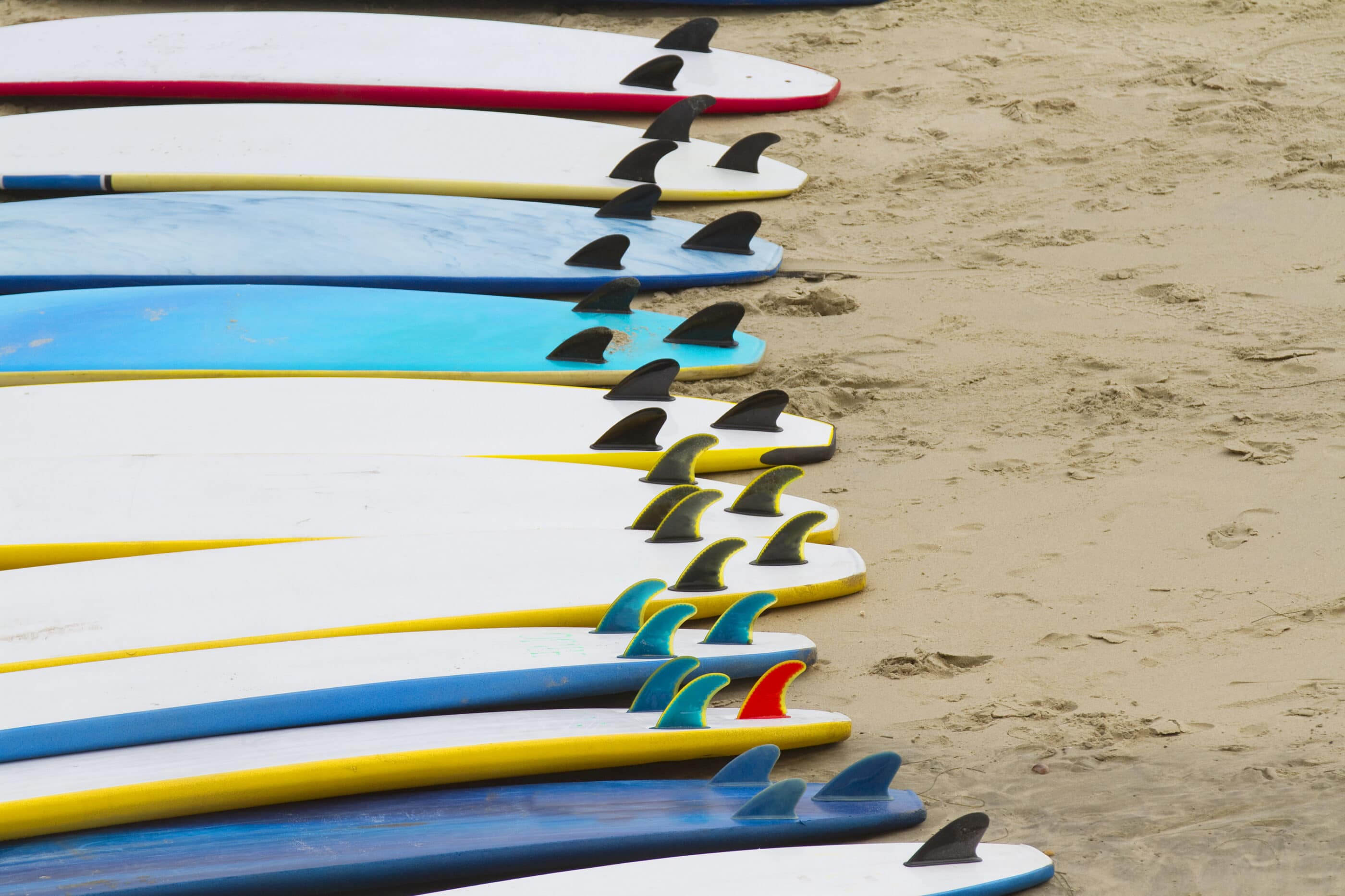 Surf boards lined up on the sand.