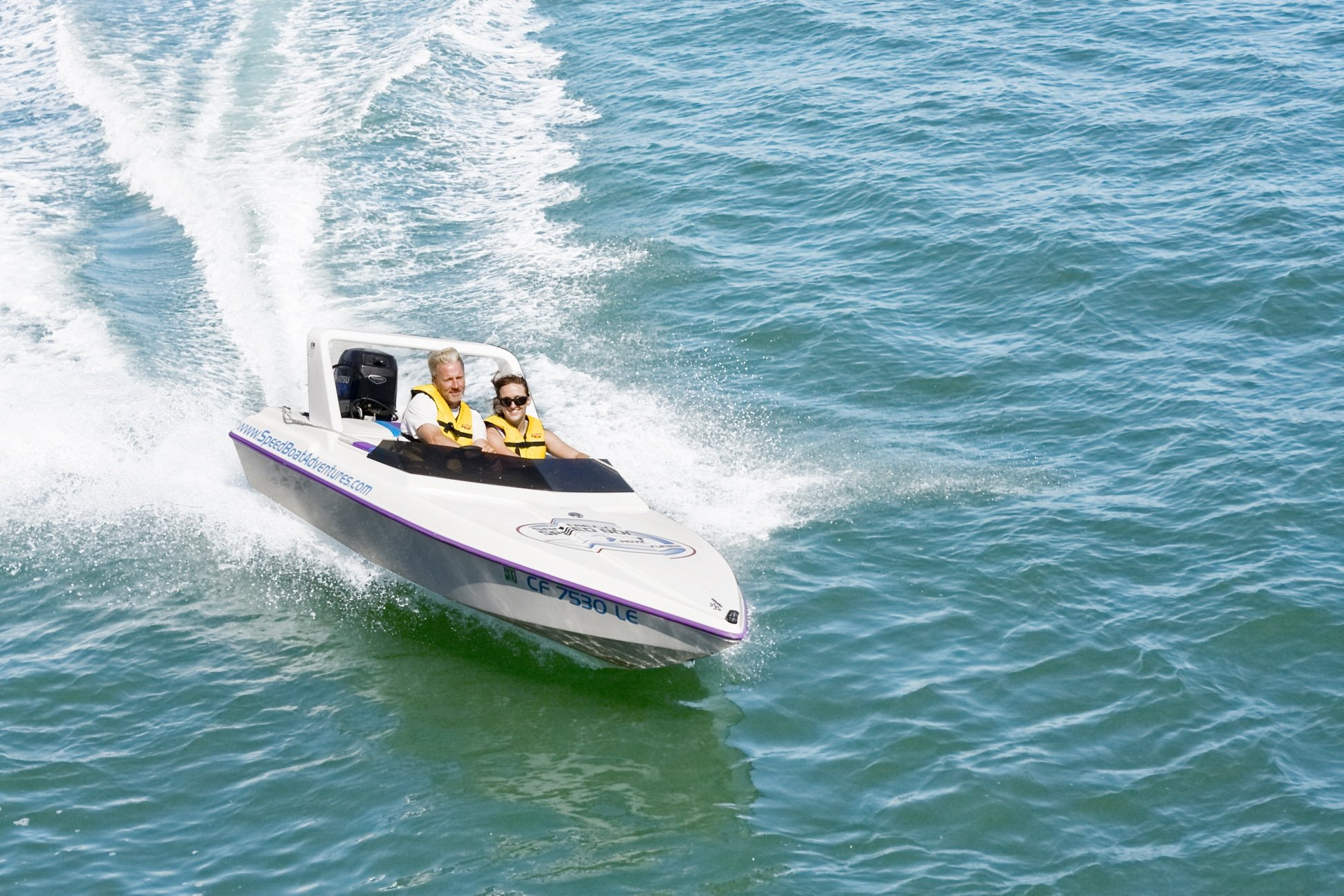 Two people drive the mini speedboat on a tour.