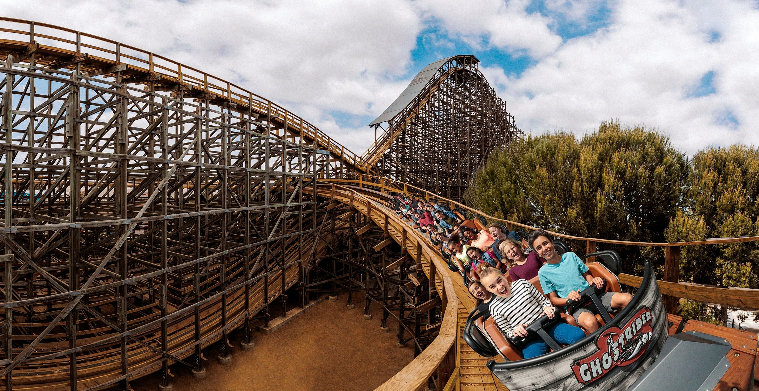 Guests ride the Ghost Rider roller coaster.