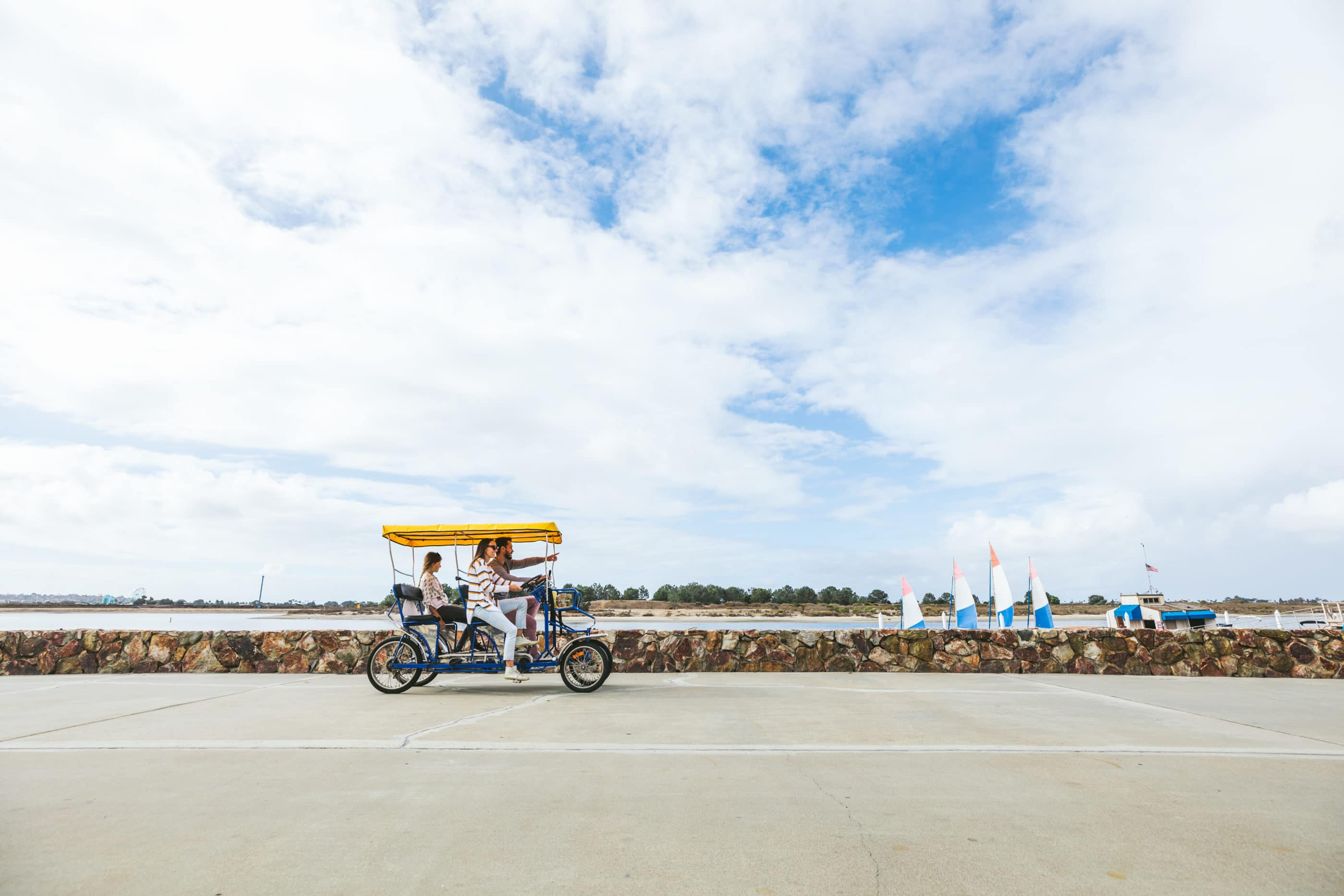A family in a surrey bike rides down the boardwalk along Mission Bay.