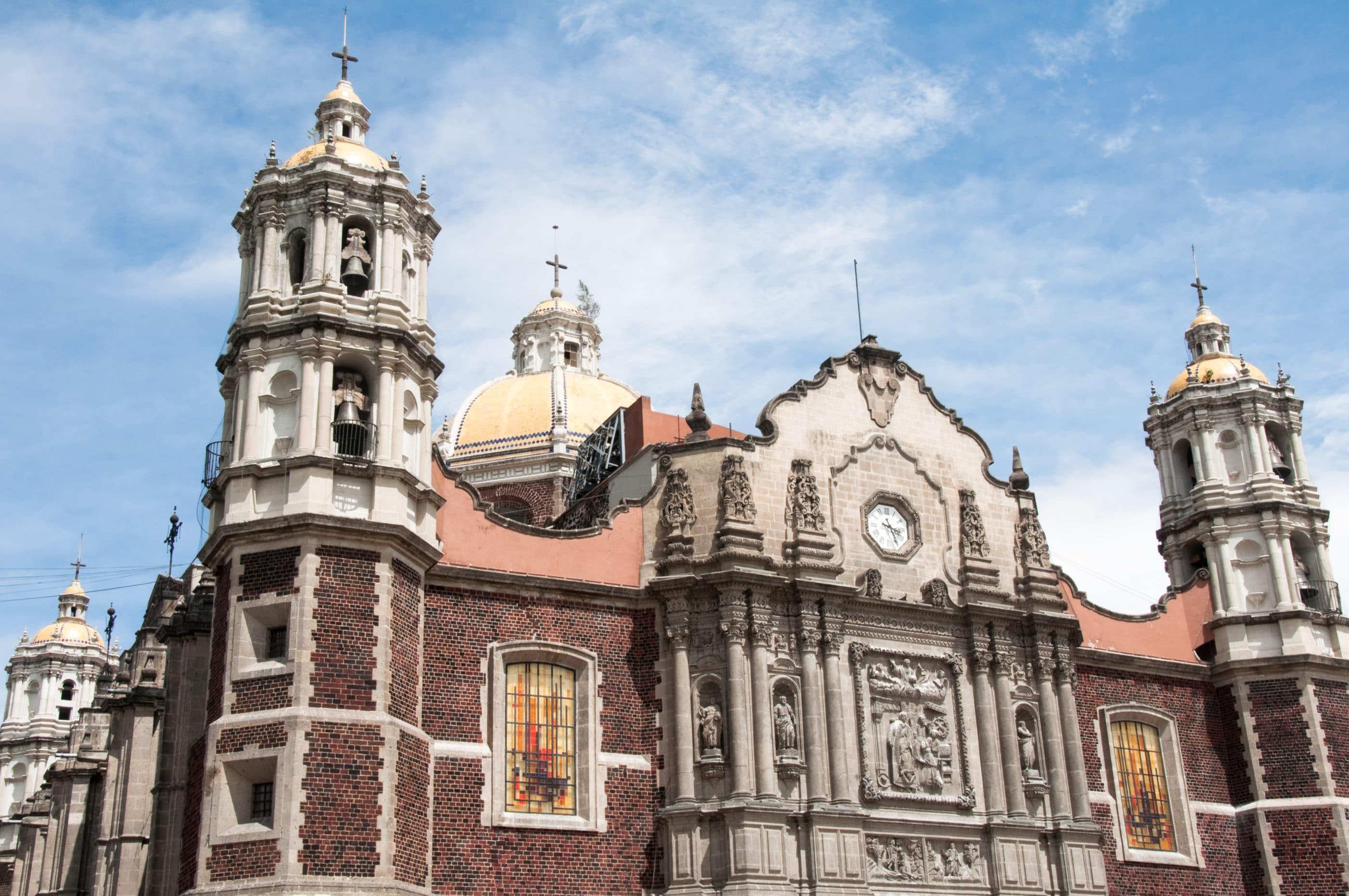 Exterior facade of the Basílica de Santa Maria de Guadalupe against the sky.