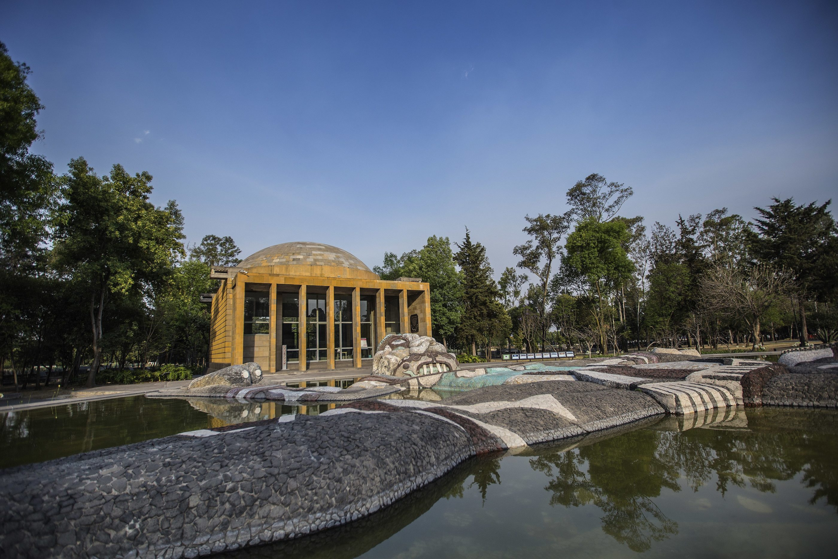 The spring with pump building in the background inside Chapultepec Forest.