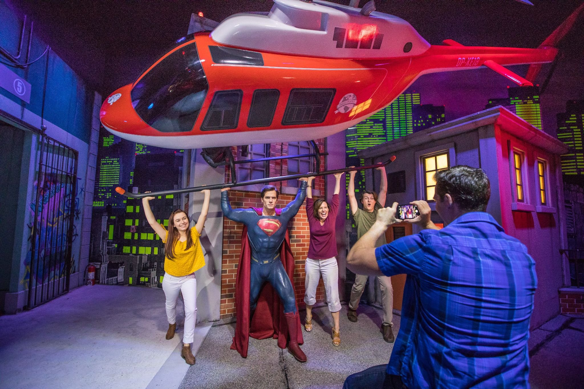 A family poses with a wax Superman at Madame Tussauds Orlando.