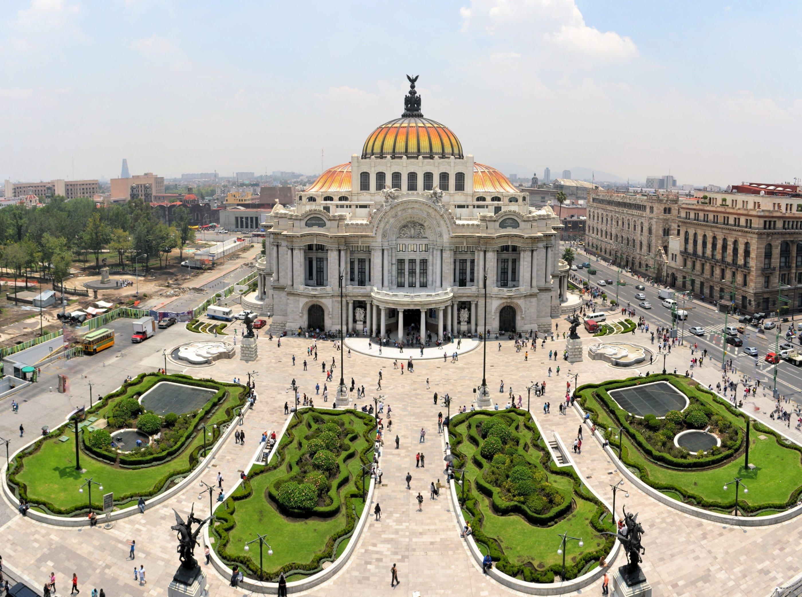 Aerial view of the Palacio de Bellas Artes in Mexico City with people walking around its exterior.